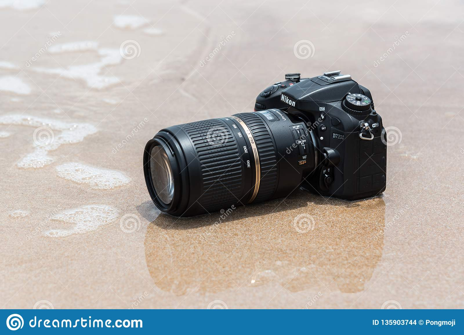 DSLR Camera On Beach Wet From Water Sea Wave Editorial Stock Image