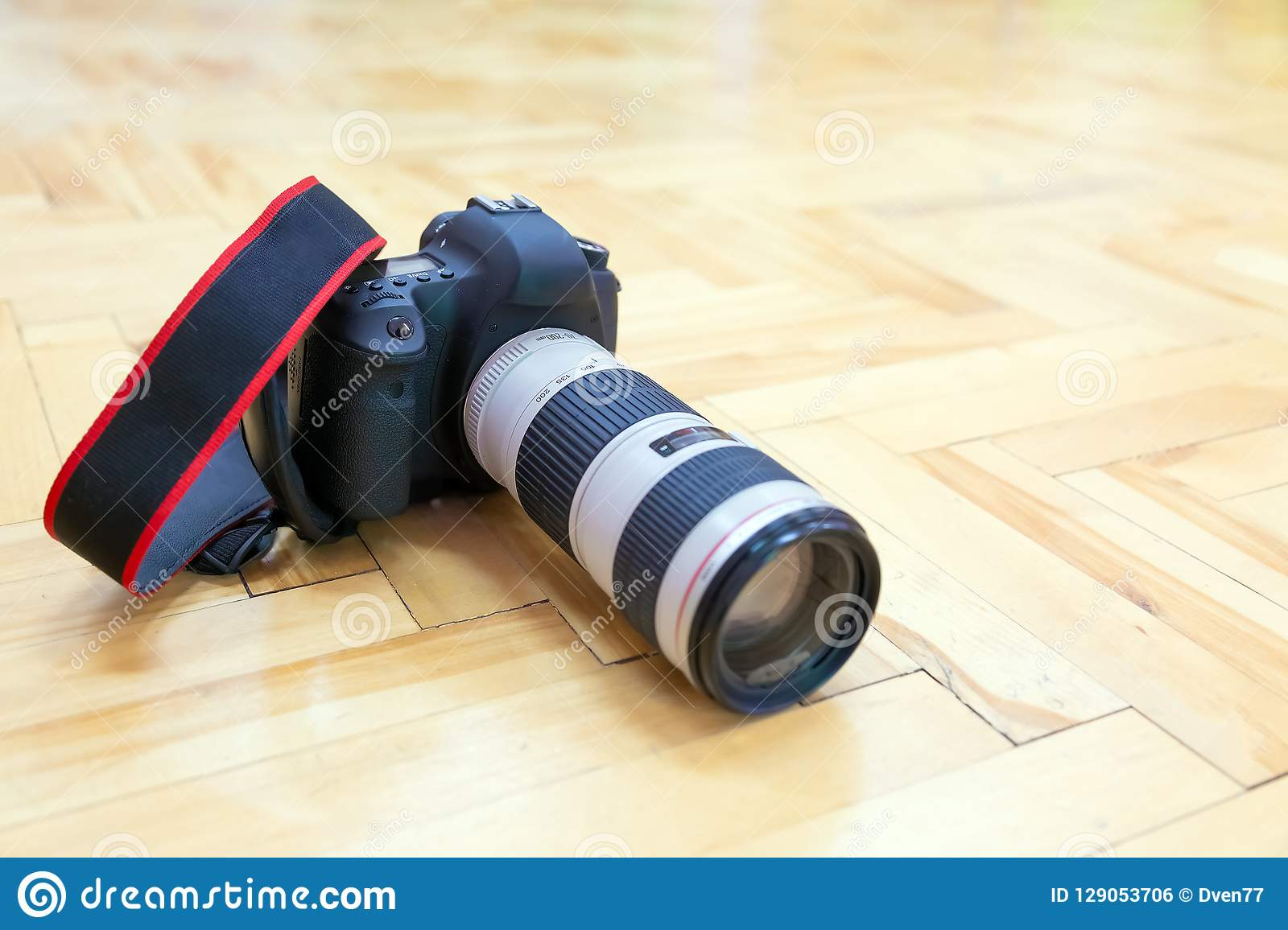 DSLR Camera With Telephoto Lens Is On The Parquet Floor