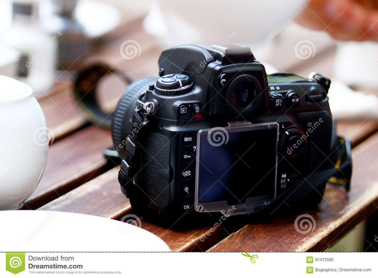 DSLR photo camera standing on table