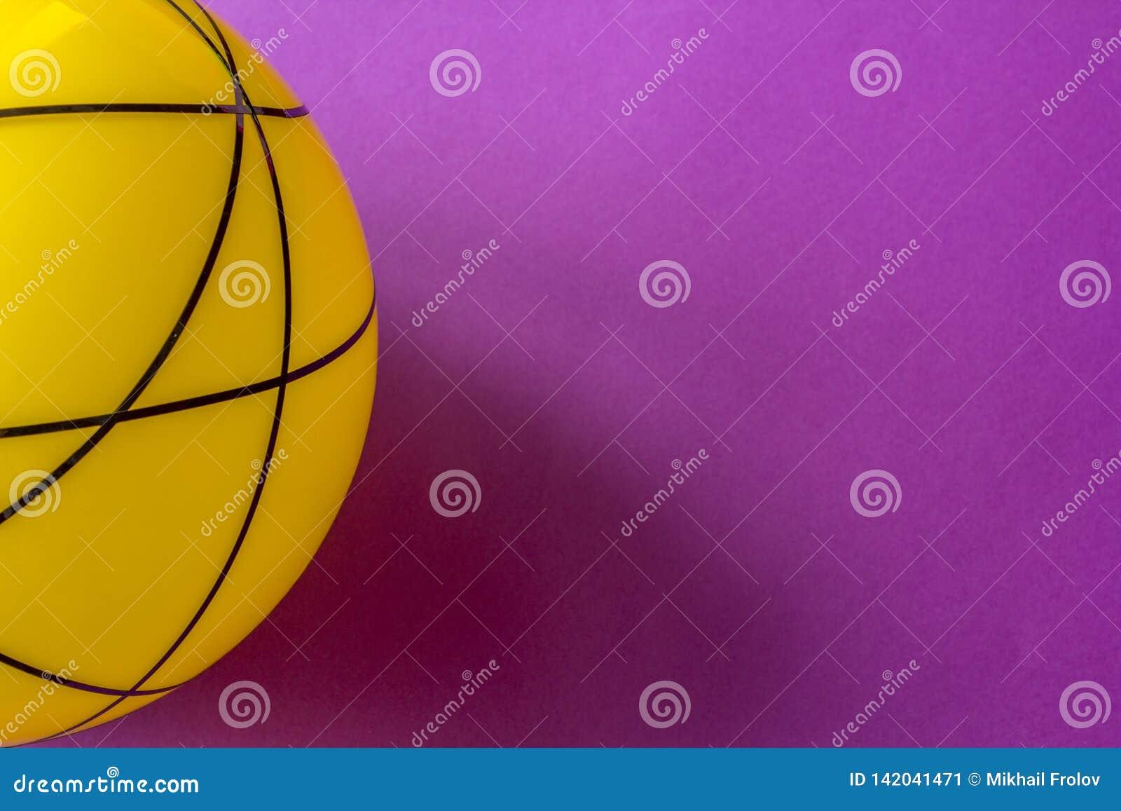 Duża żółta szklana piłka na fiołkowym tle Wciąż życie pasiasta żółta piłka na jaskrawym fiołka stole