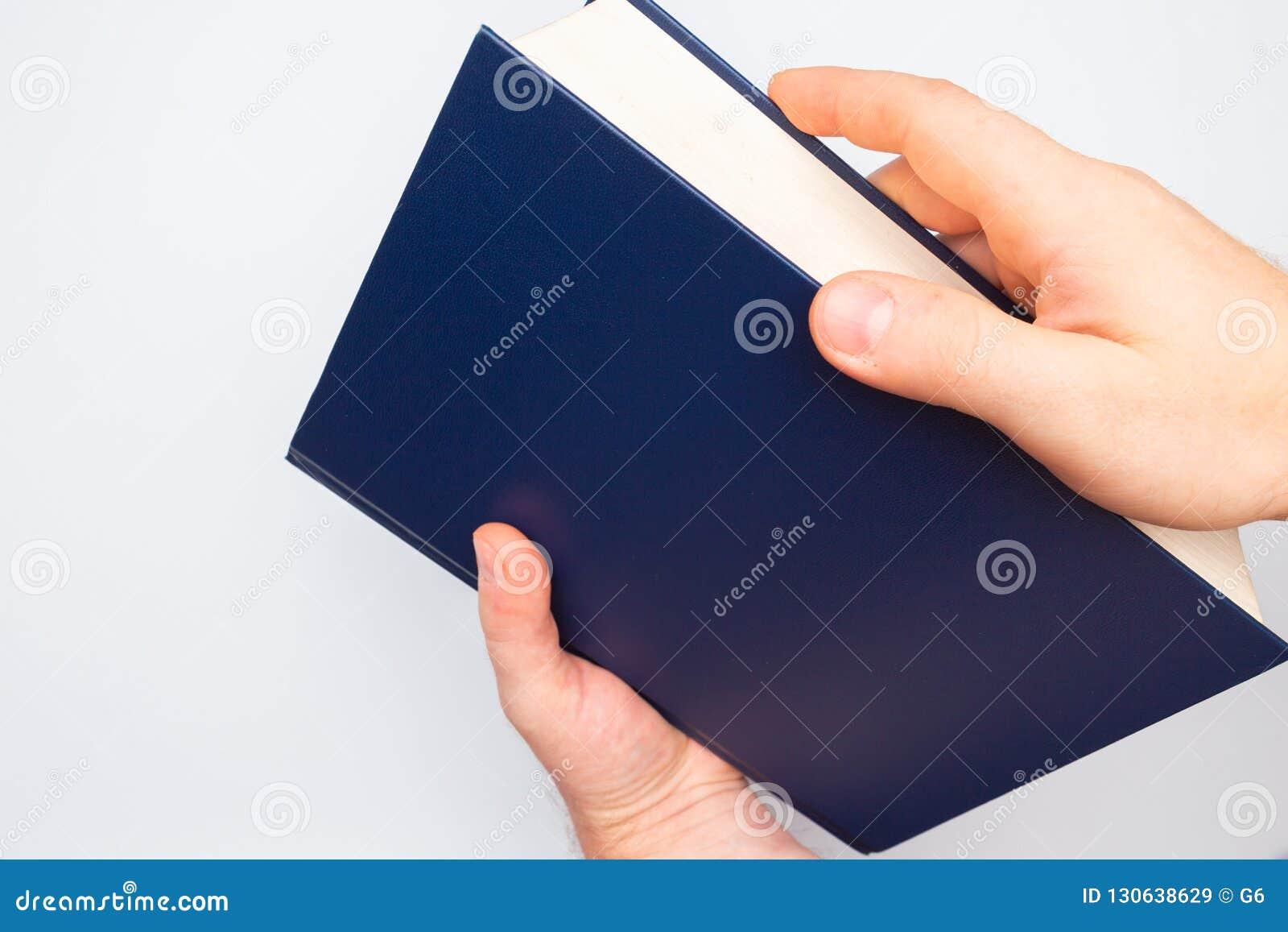 Duża ciężka błękitna książka w rękach