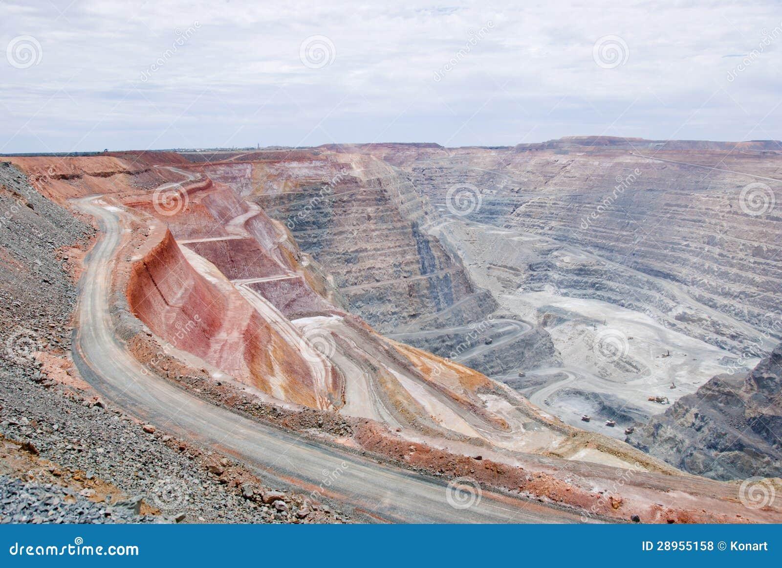 Duża kopalniana jama z małymi usyp ciężarówkami i czerwonawą ziemią