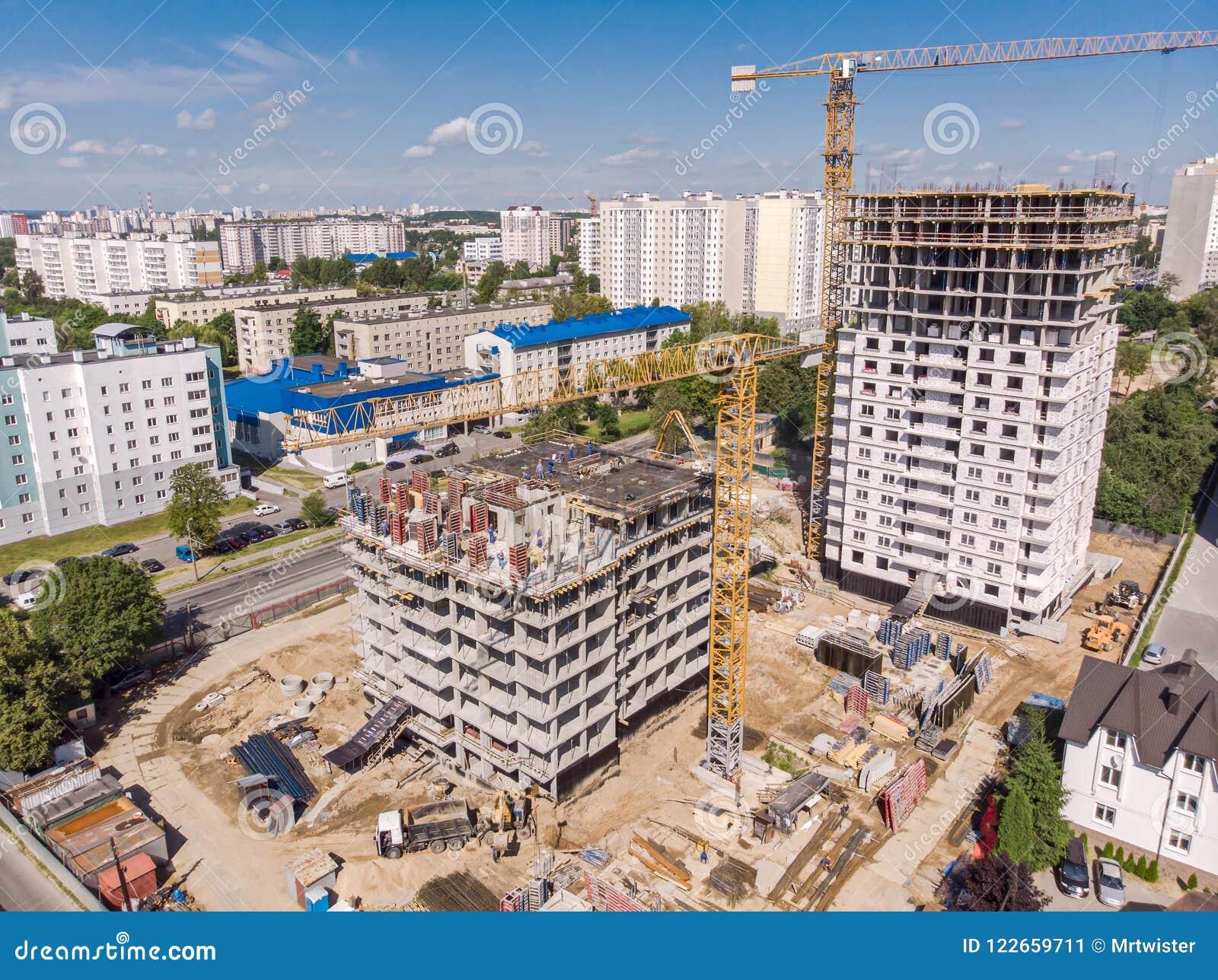 Duża miasto budowa z żurawiami, maszynerią i pracownikami,