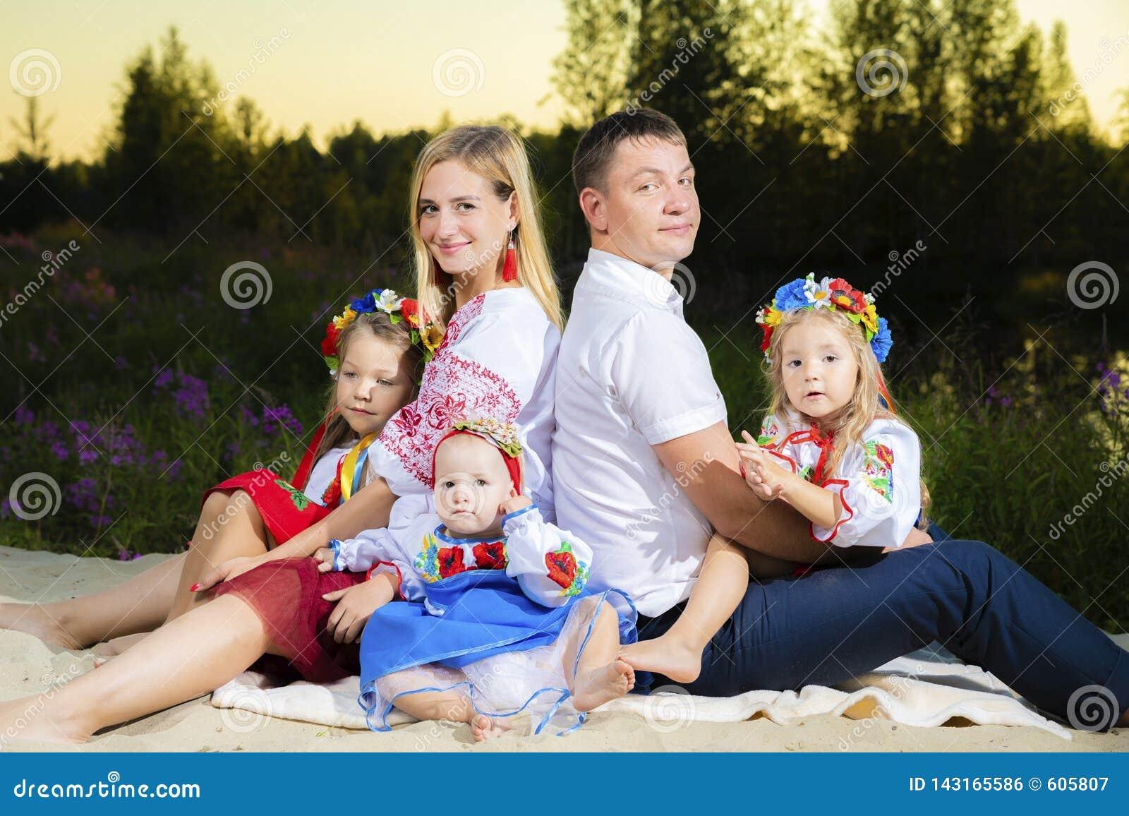 Duża rodzina w etnicznych Ukraińskich kostiumach siedzi na łące pojęcie duża rodzina
