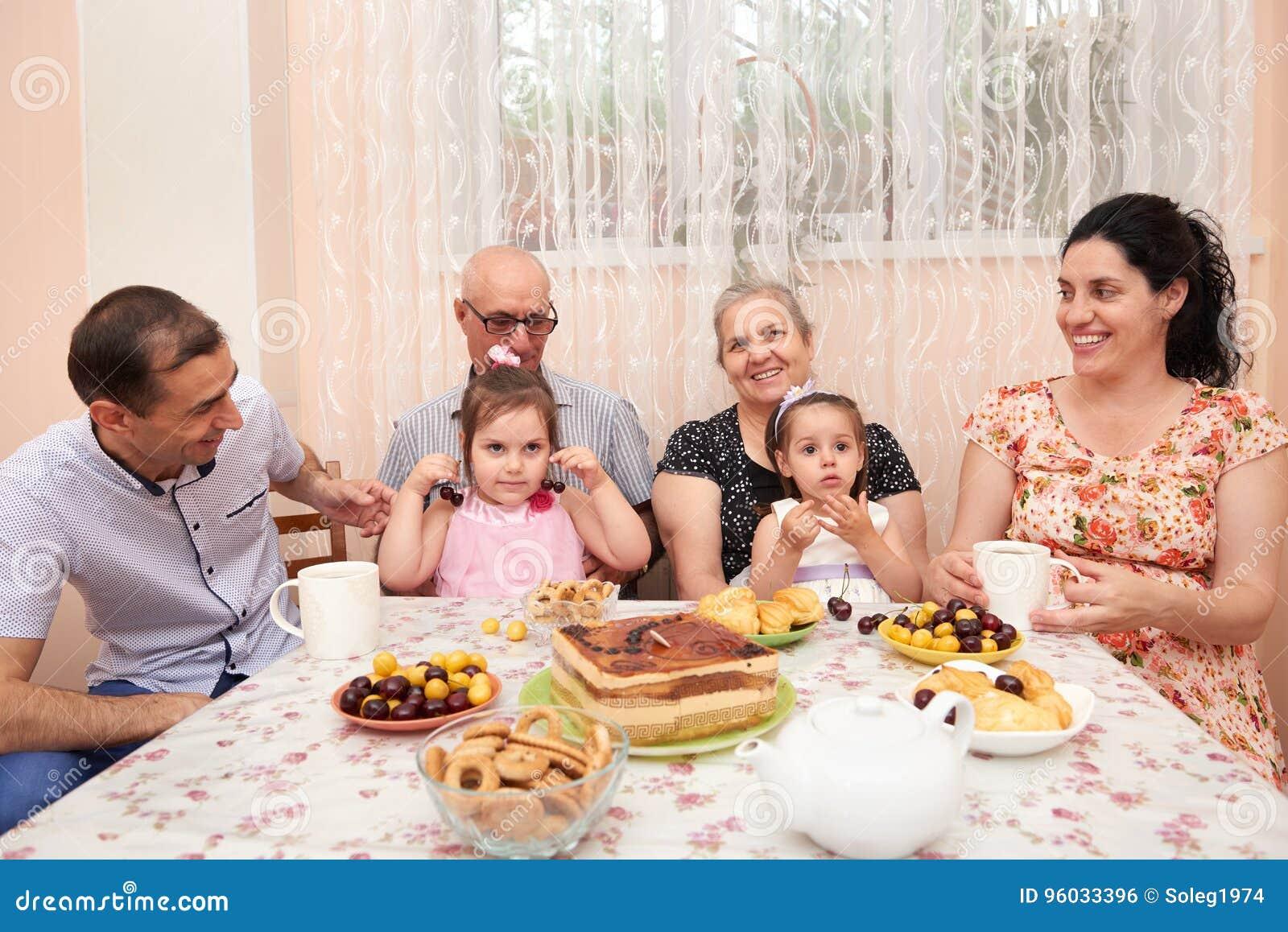 Duża rodzinna pije herbata w jadalni