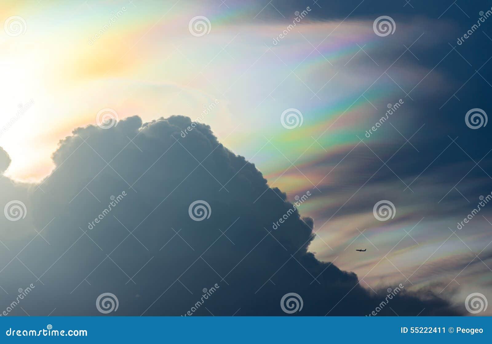 Duża tęczy chmura i mały samolot