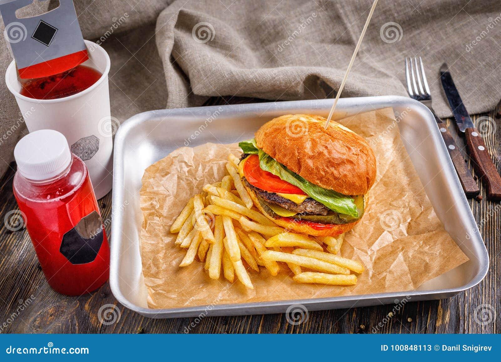 Duży hamburger z trzy wołowiny warzywami z i cutlet złotymi crispy francuzów dłoniakami i wznoszącą toast crispy grzanką na drewn