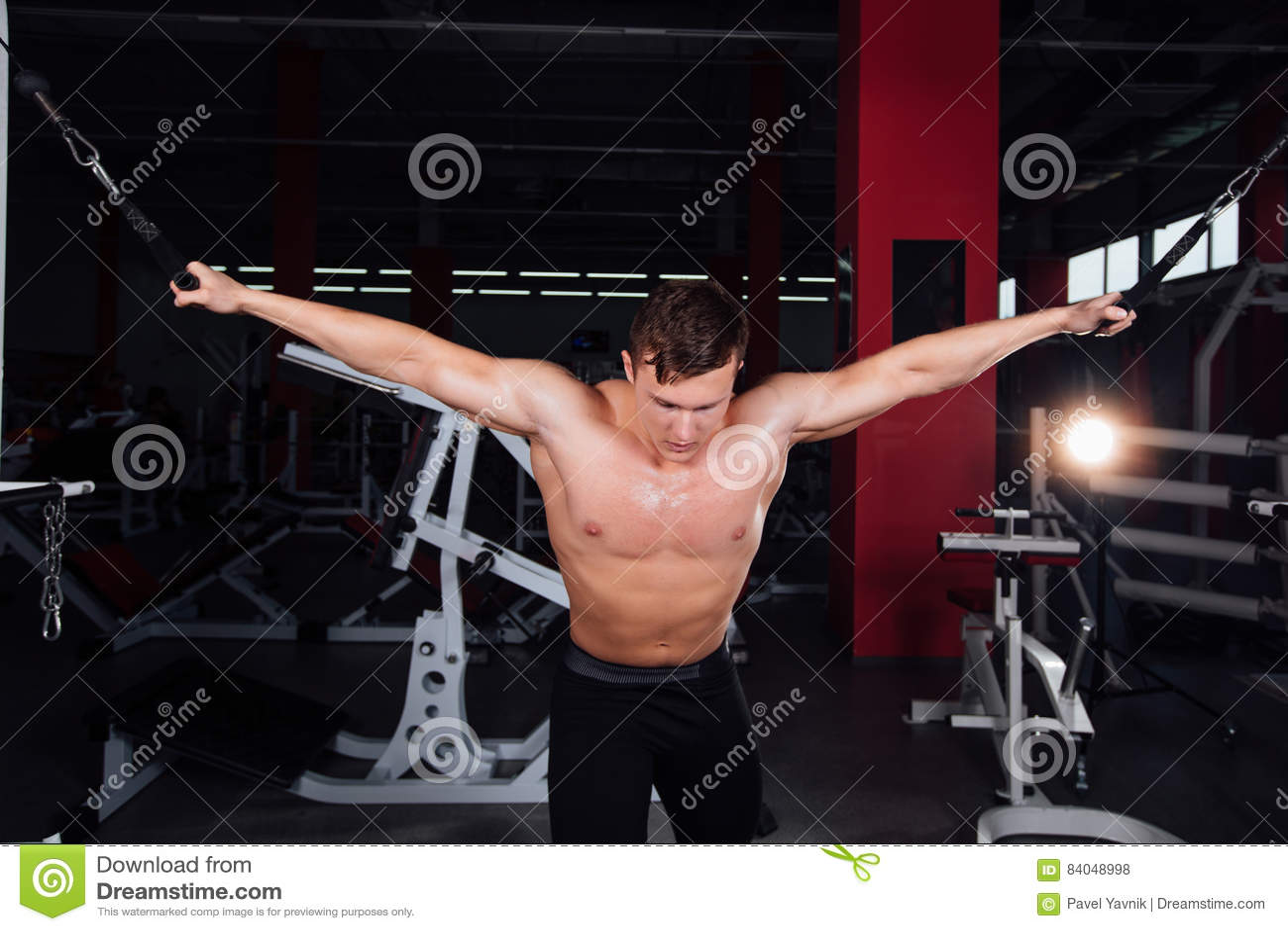 Duży silny bodybuider bez koszula demonstruje skrzyżowań ćwiczenia Ciężki szkolenie i