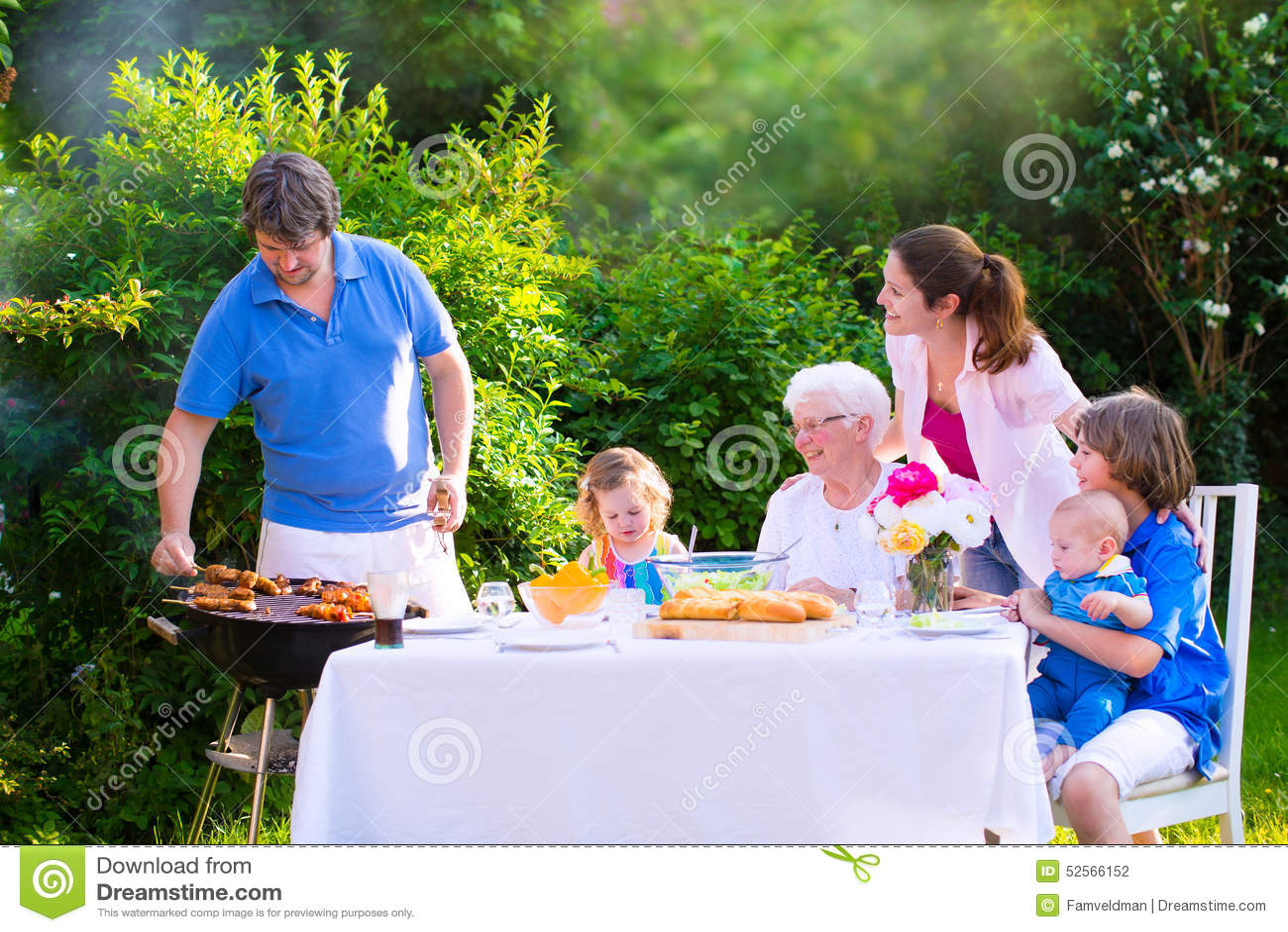 Duży szczęśliwy rodzinny cieszy się bbq grill w ogródzie