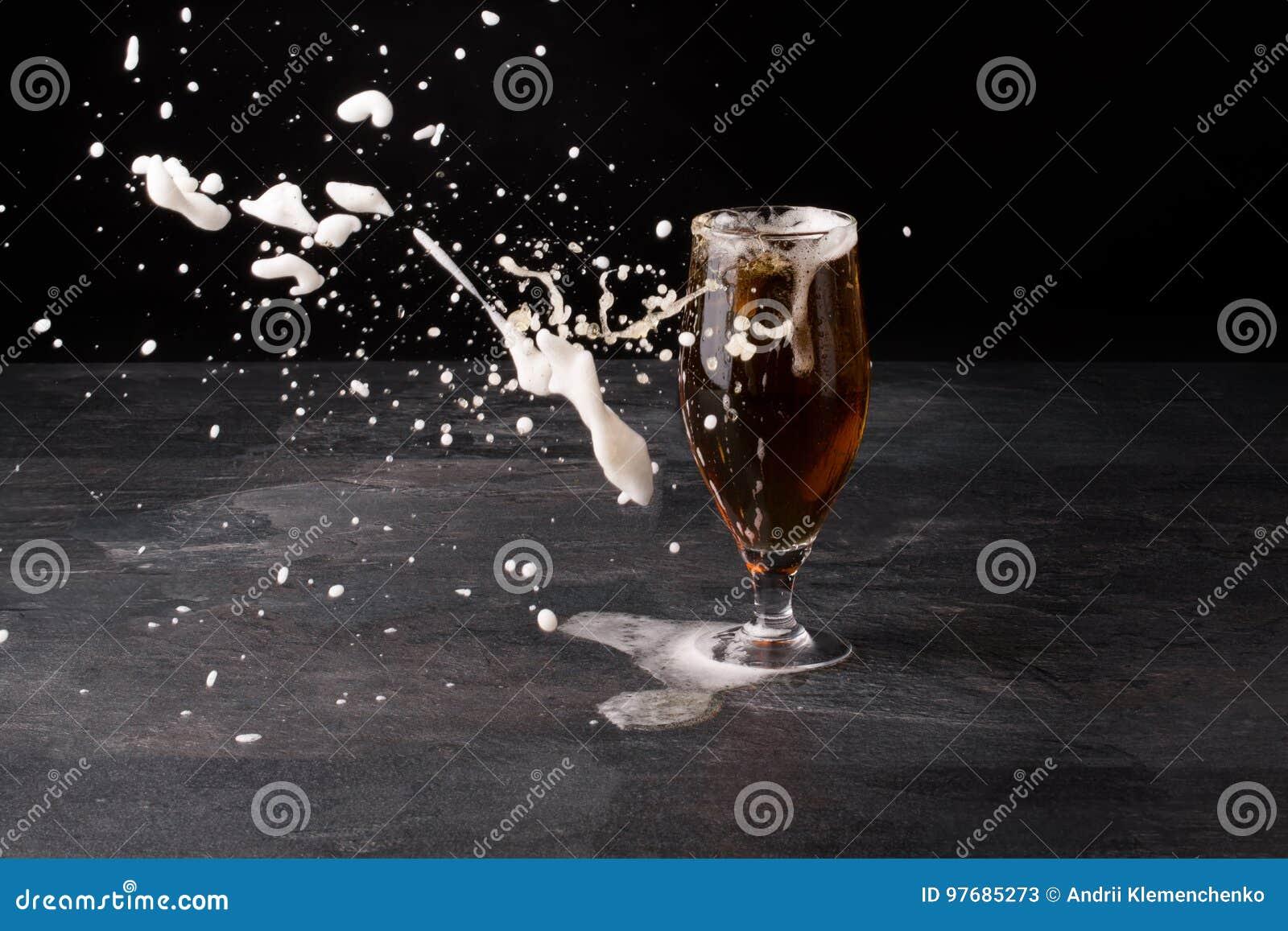 Duży szkło piwny pełny z brown ale i z biel pianą blowed daleko od na ciemnym kamiennym tle Alkoholu napój
