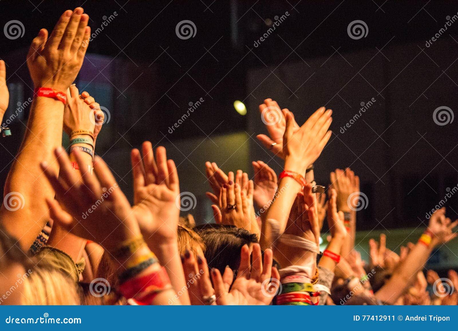 Duży tłum klascze z rękami w powietrzu przy rockowym festiwalem