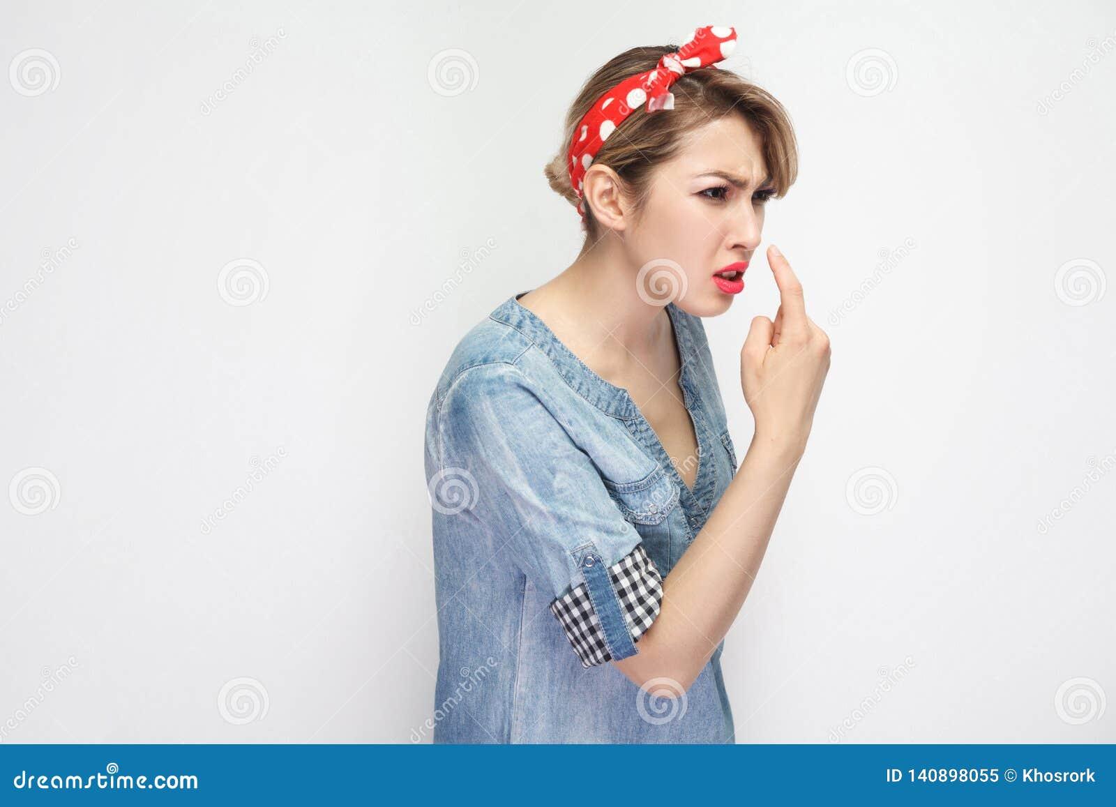 Du är lögnaren Stående av den ilskna härliga unga kvinnan i tillfällig blå grov bomullstvillskjorta med makeup och rött huvudbind