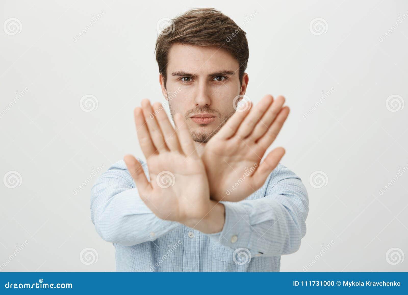 Du kan inte bryta regler Ståenden av strikt korsat säkert stiligt europeiskt dra för grabb gömma i handflatan in mot kamera i ing