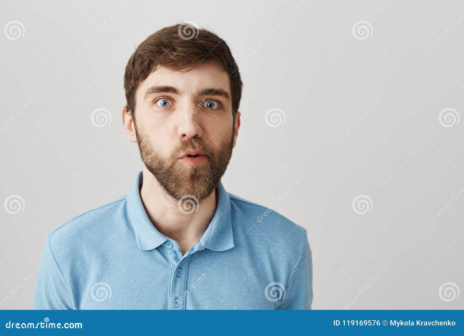 Du måste skoja Stående av den förvirrade gulliga skäggiga grabben som står med tvivelaktigt och ifrågasatt uttryck, flyttande käk