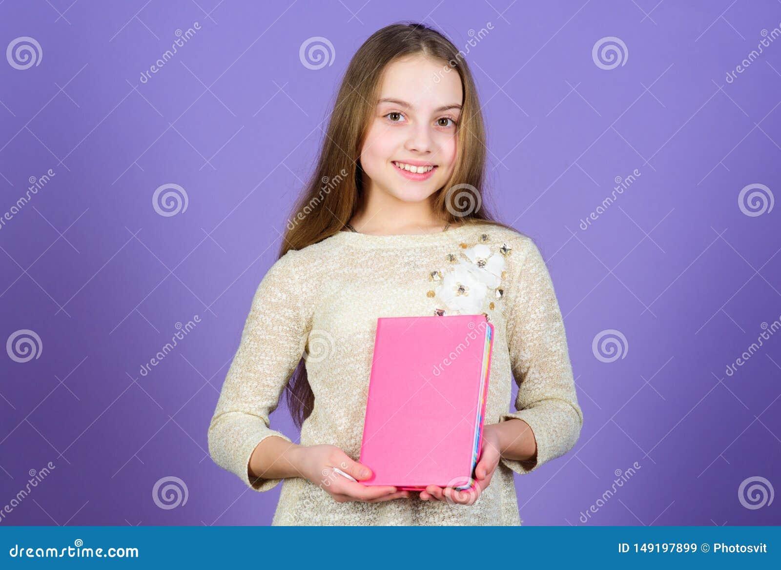 Du v?lter f?r att ber?tta en bok vid dess r?kning F?rtjusande liten flickainnehavbok Gulligt sm?barn med boken i h?nder Hon tycke