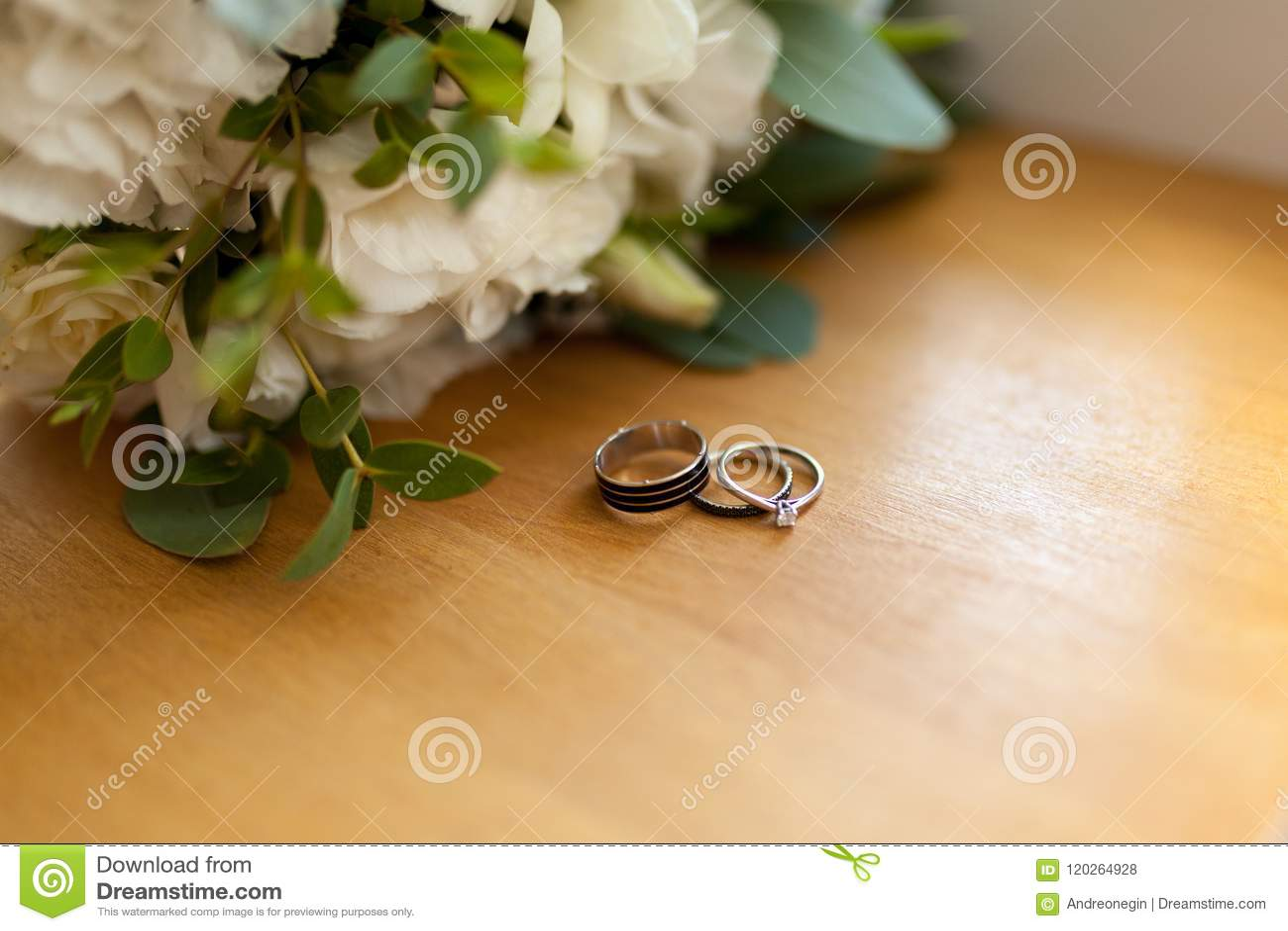 Duas alianças de casamento da platina no fundo de madeira com flores Anel da noiva com diamantes Foco raso Rústico wed o conceito