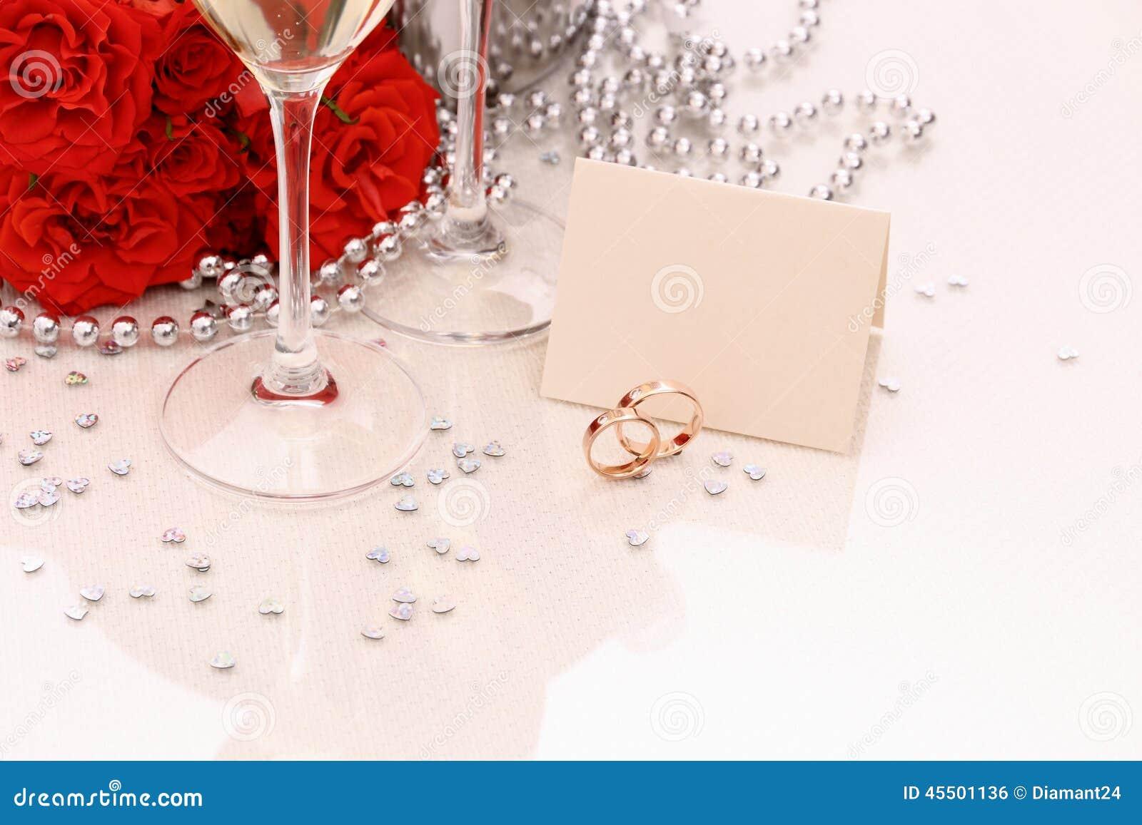 Duas alianças de casamento douradas com cartão, vidros do champanhe