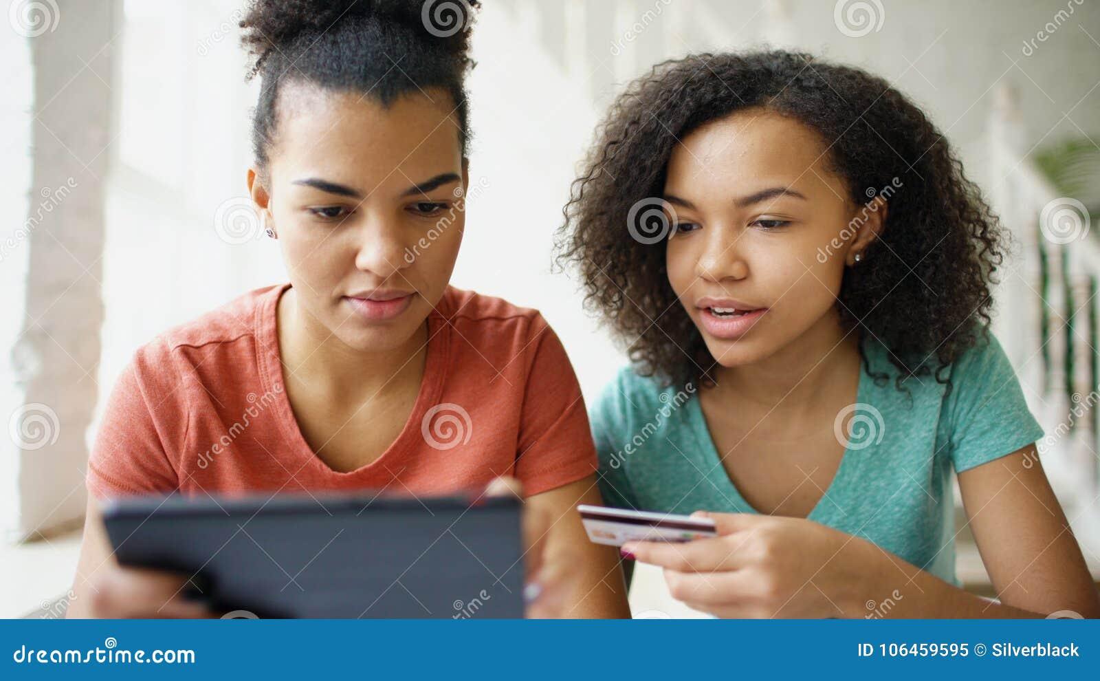 Duas amigas encaracolado alegres da raça misturada que compram em linha com tablet pc e cartão de crédito em casa