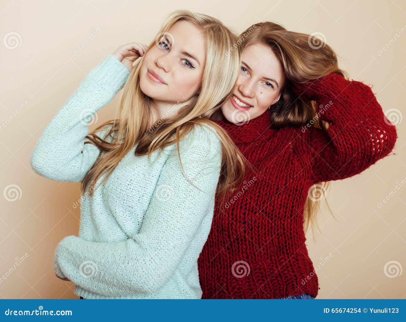 Duas amigas novas nas camisetas do inverno dentro que têm o divertimento lifestyle Os amigos adolescentes louros fecham-se acima
