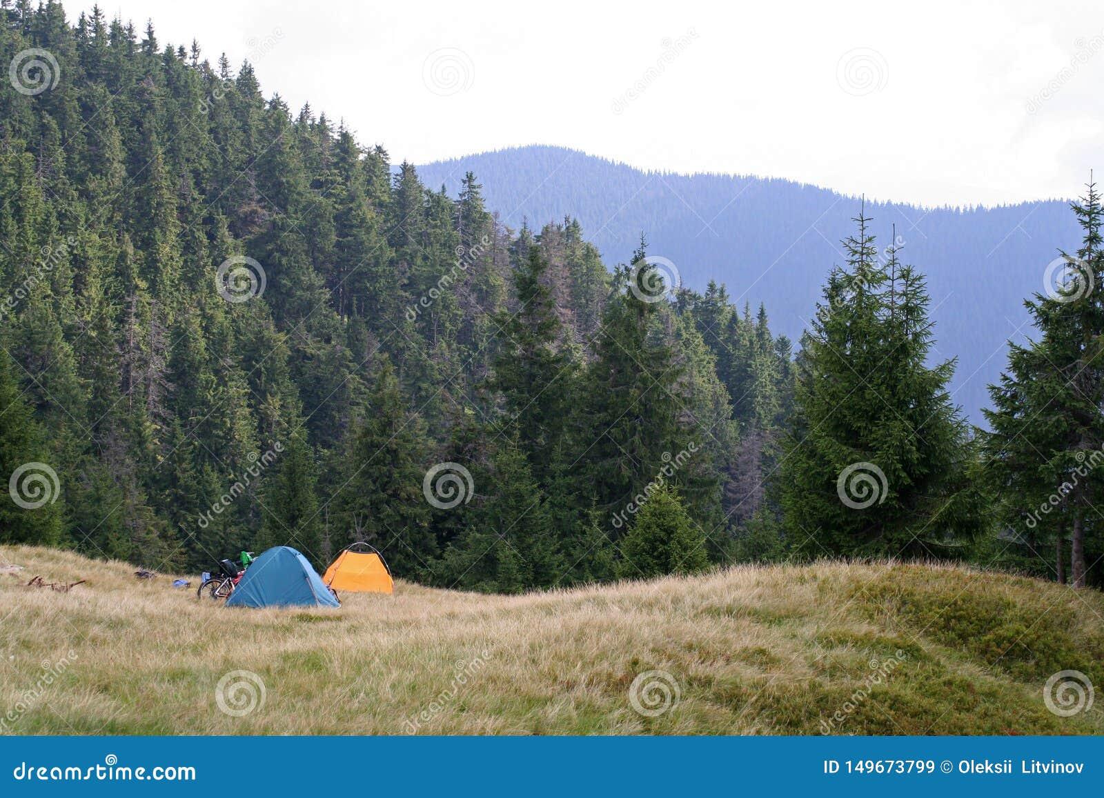 Duas barracas e bicicletas em um prado nas montanhas