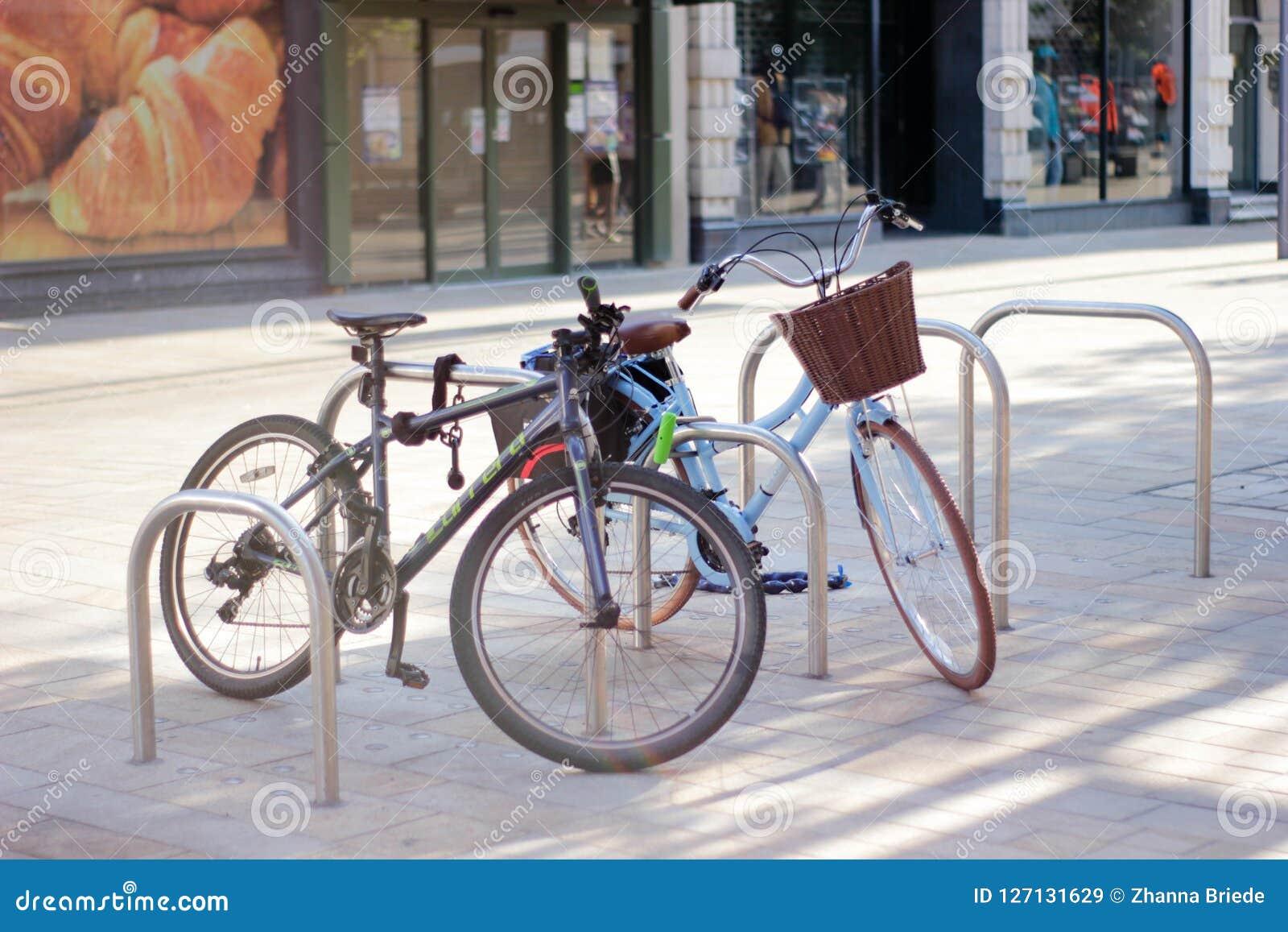 Duas bicicletas são estacionadas em um estacionamento especial da bicicleta em uma cidade inglesa pequena