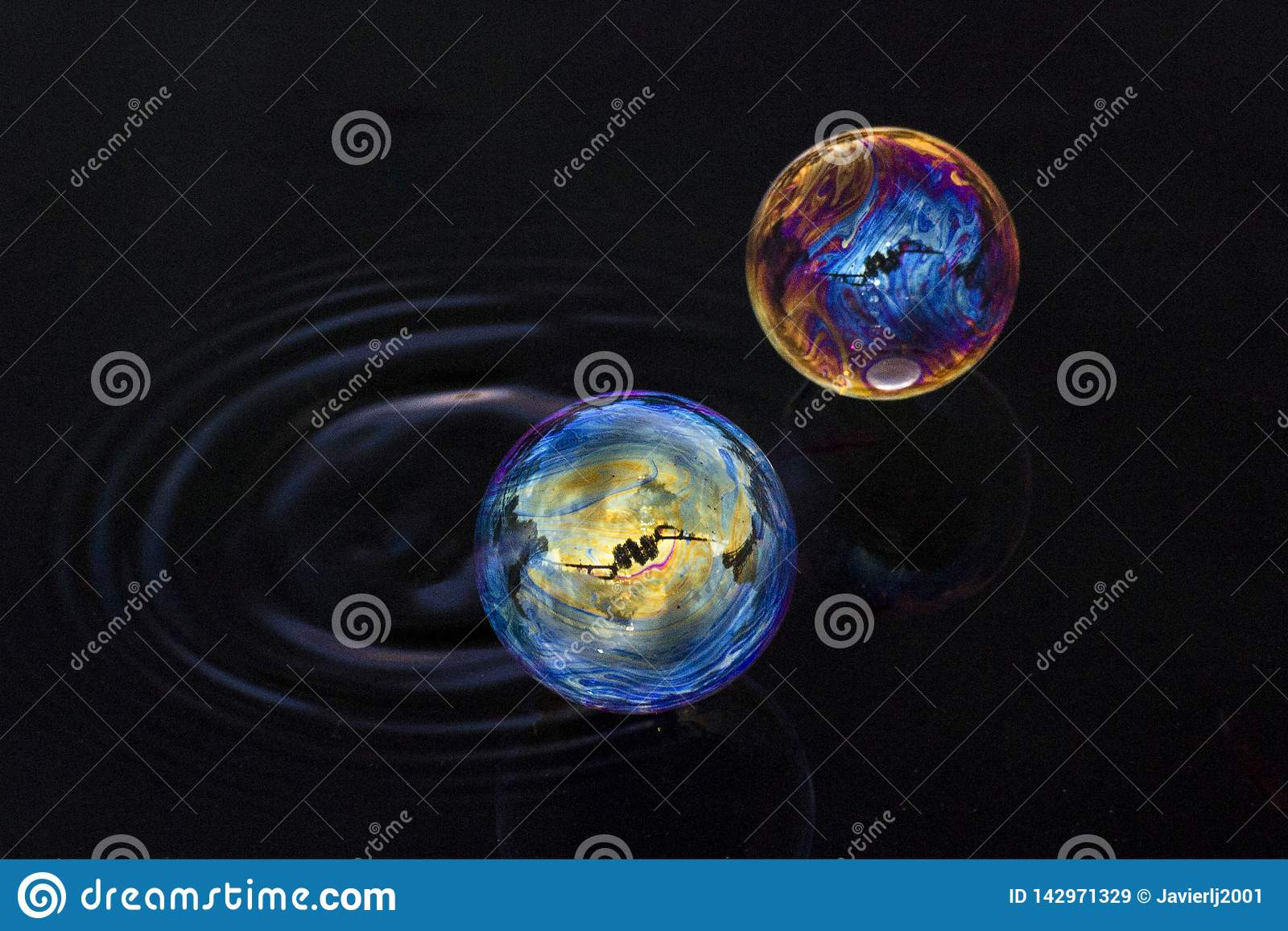 Duas bolhas das cores diferentes que flutuam sobre a água