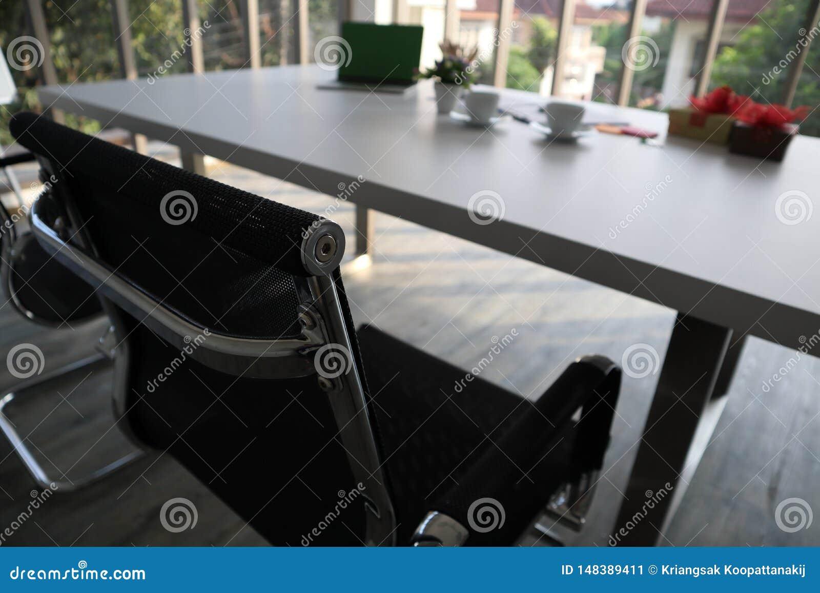 Duas cadeiras pretas e tabela branca e outros materiais