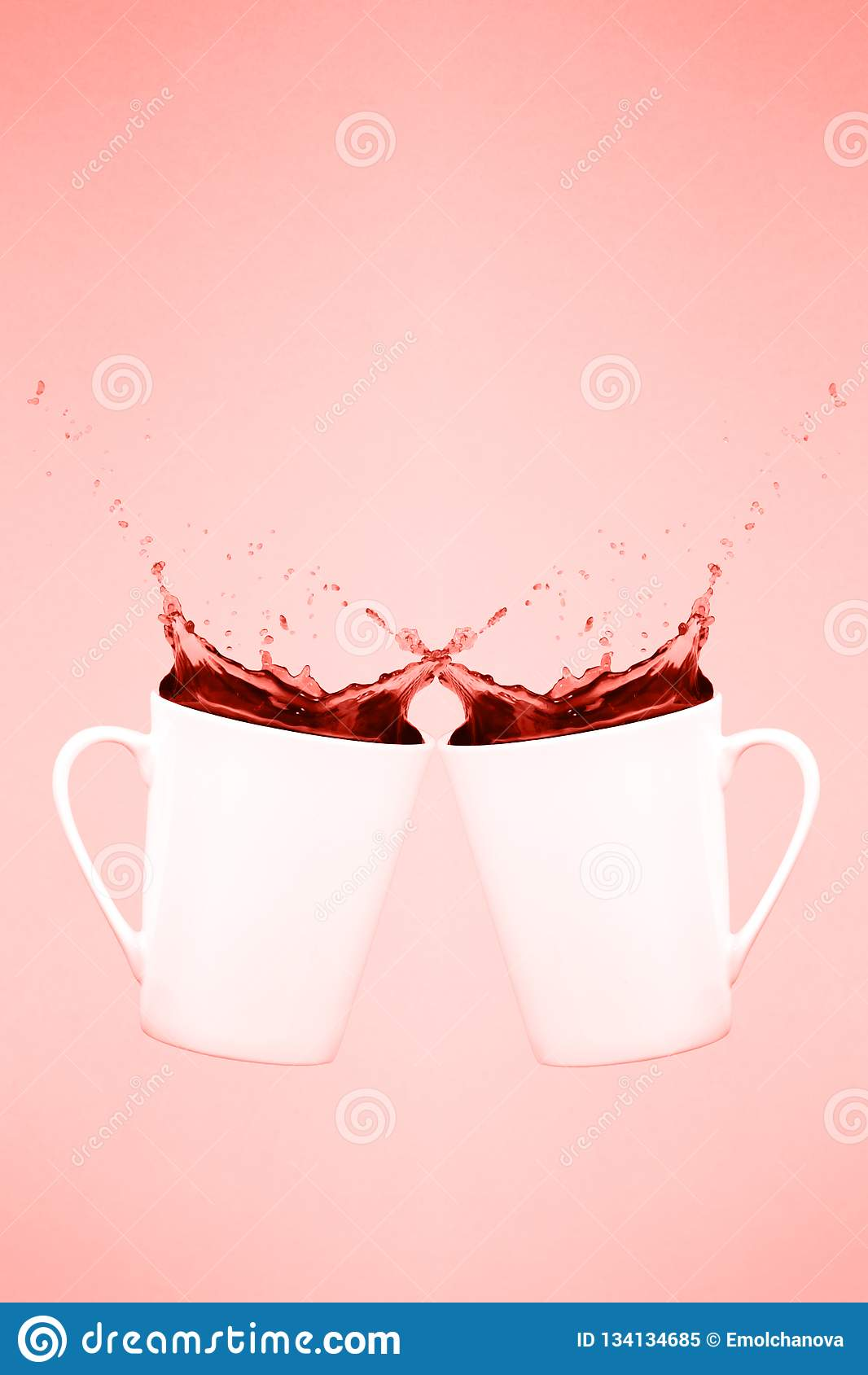Duas canecas de café levitando com espirram Conceito do café Tendência mínima da arte Fundo cor-de-rosa contínuo Tema coral de vi