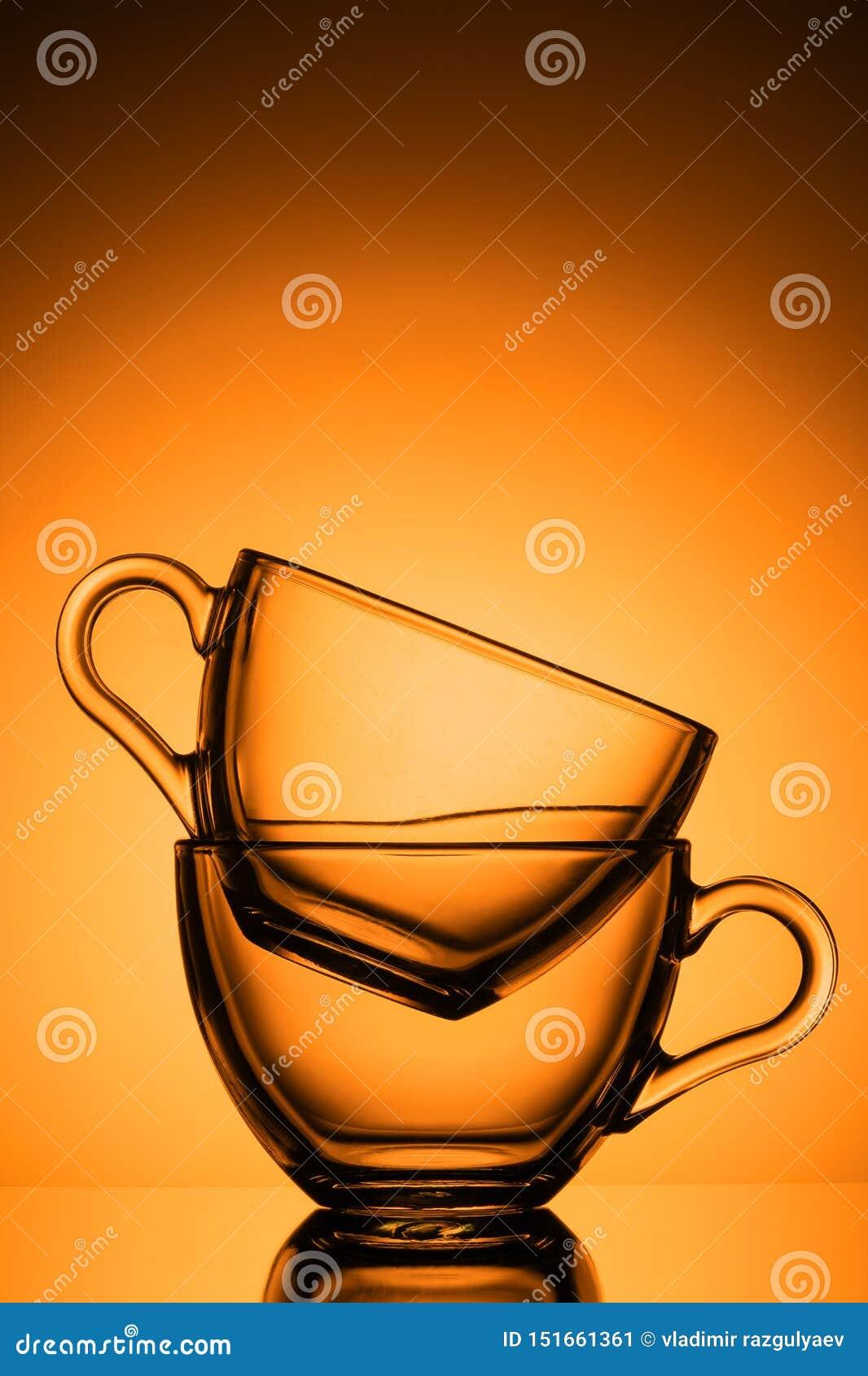 Duas canecas de vidro transparentes para o chá Fundo alaranjado, close-up, disposição vertical