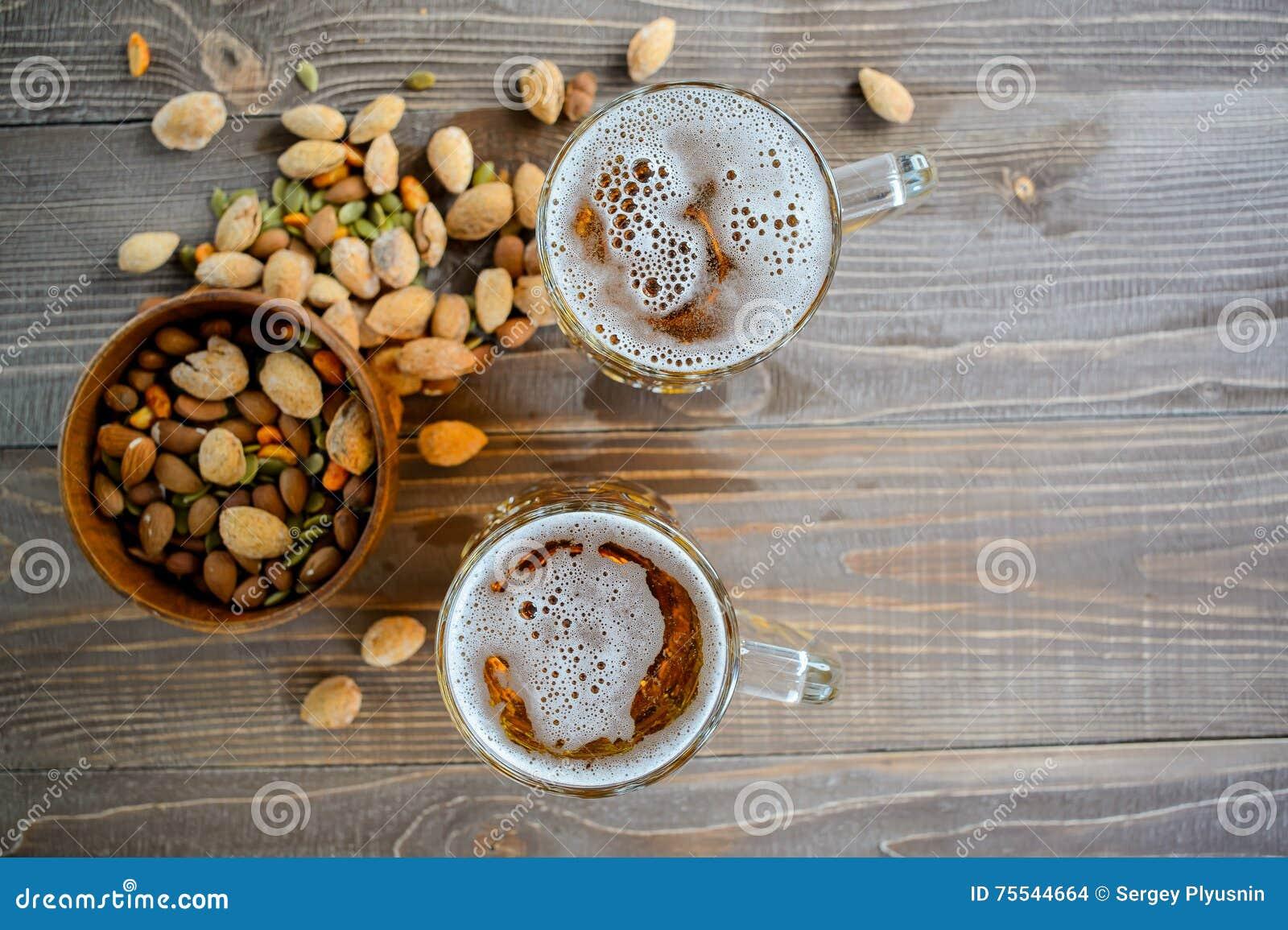 Duas cervejas de Oktoberfest com porcas de pistache em uma tabela de madeira