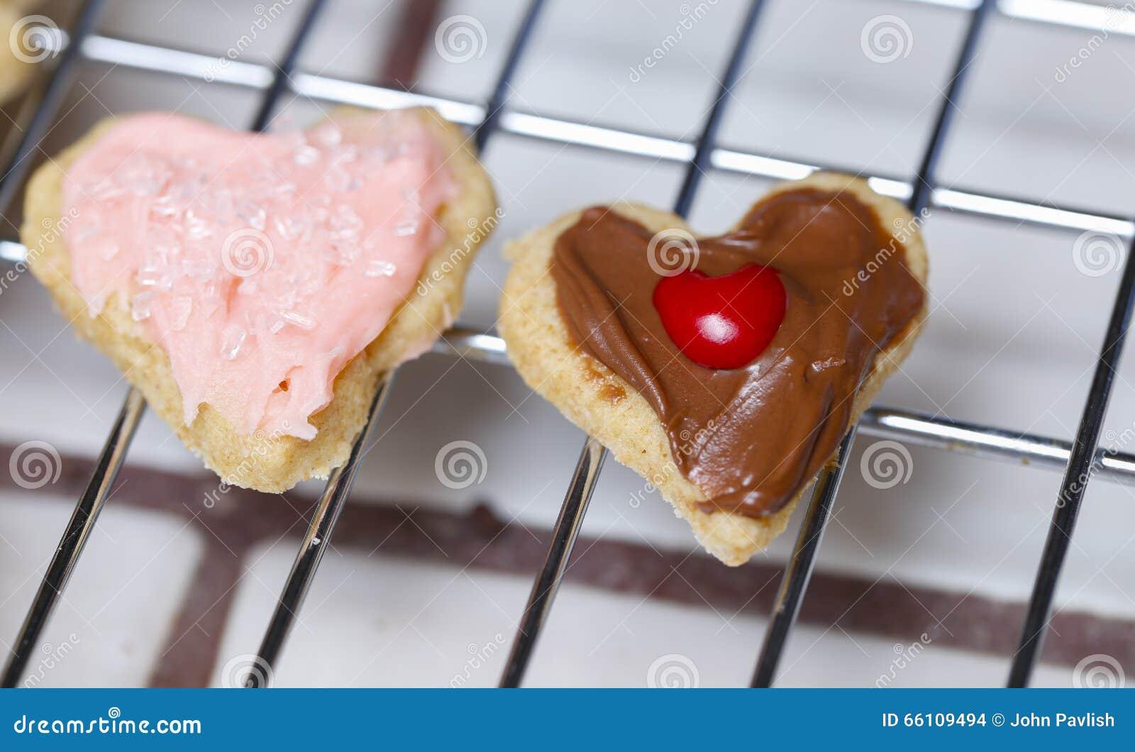 Duas cookies adoráveis bonitos pequenas do Valentim do coração Um no rosa para