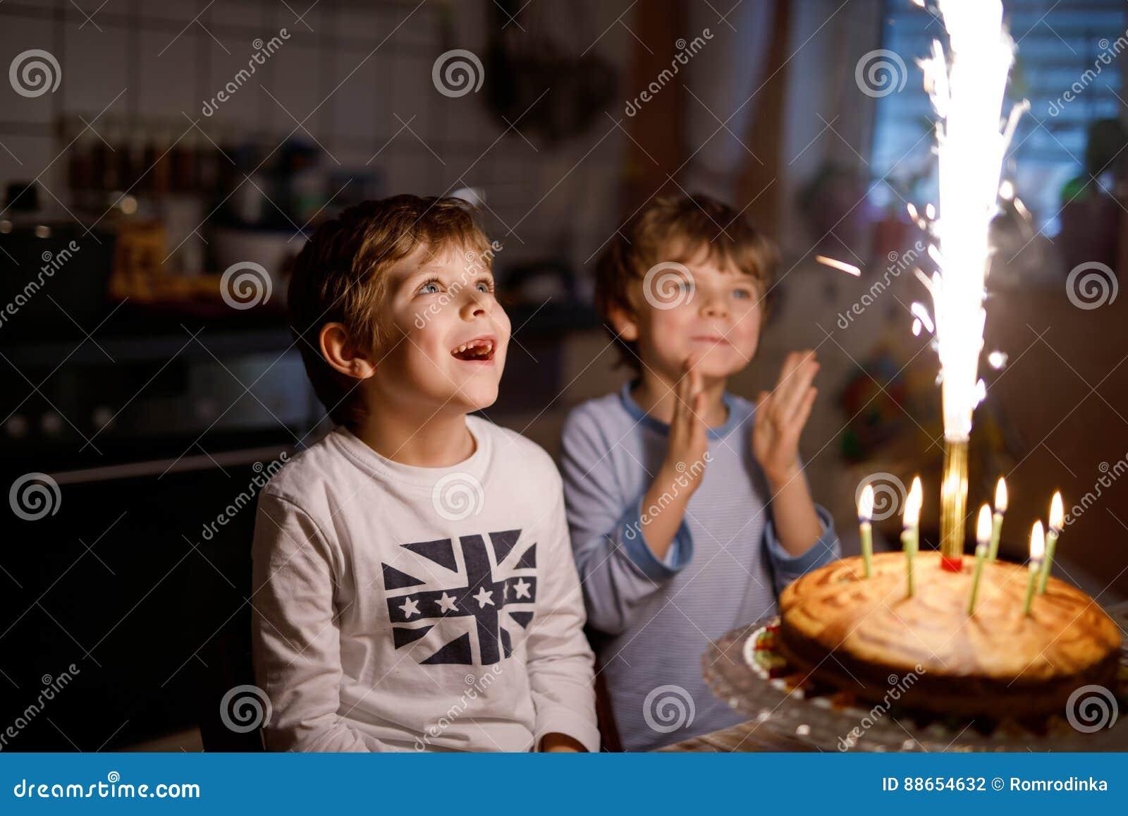 Duas crianças bonitas, meninos prées-escolar pequenos que comemoram o aniversário e que fundem velas