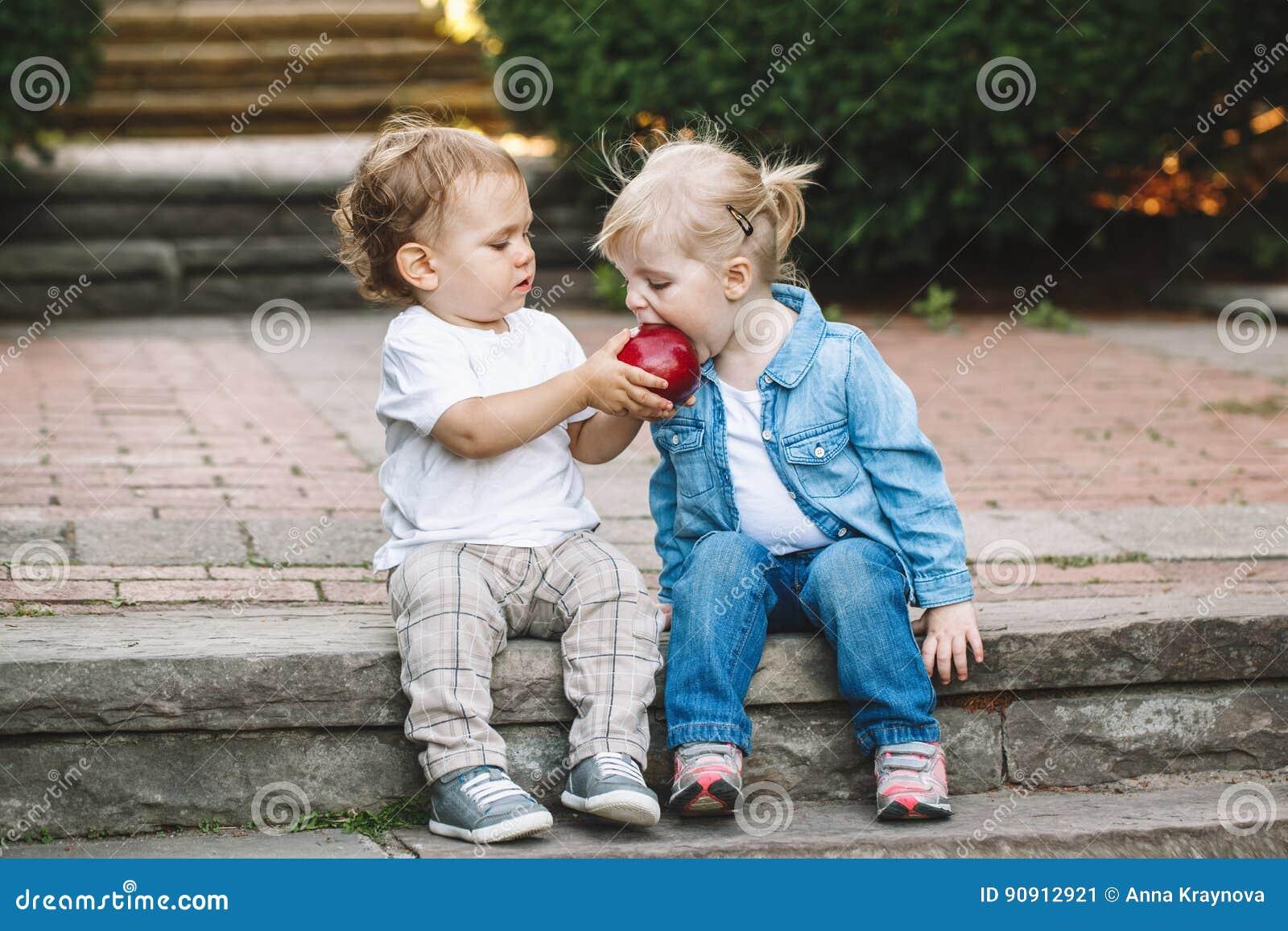 Duas crianças engraçadas adoráveis bonitos caucasianos brancas das crianças que sentam junto a partilha comendo o alimento da maç