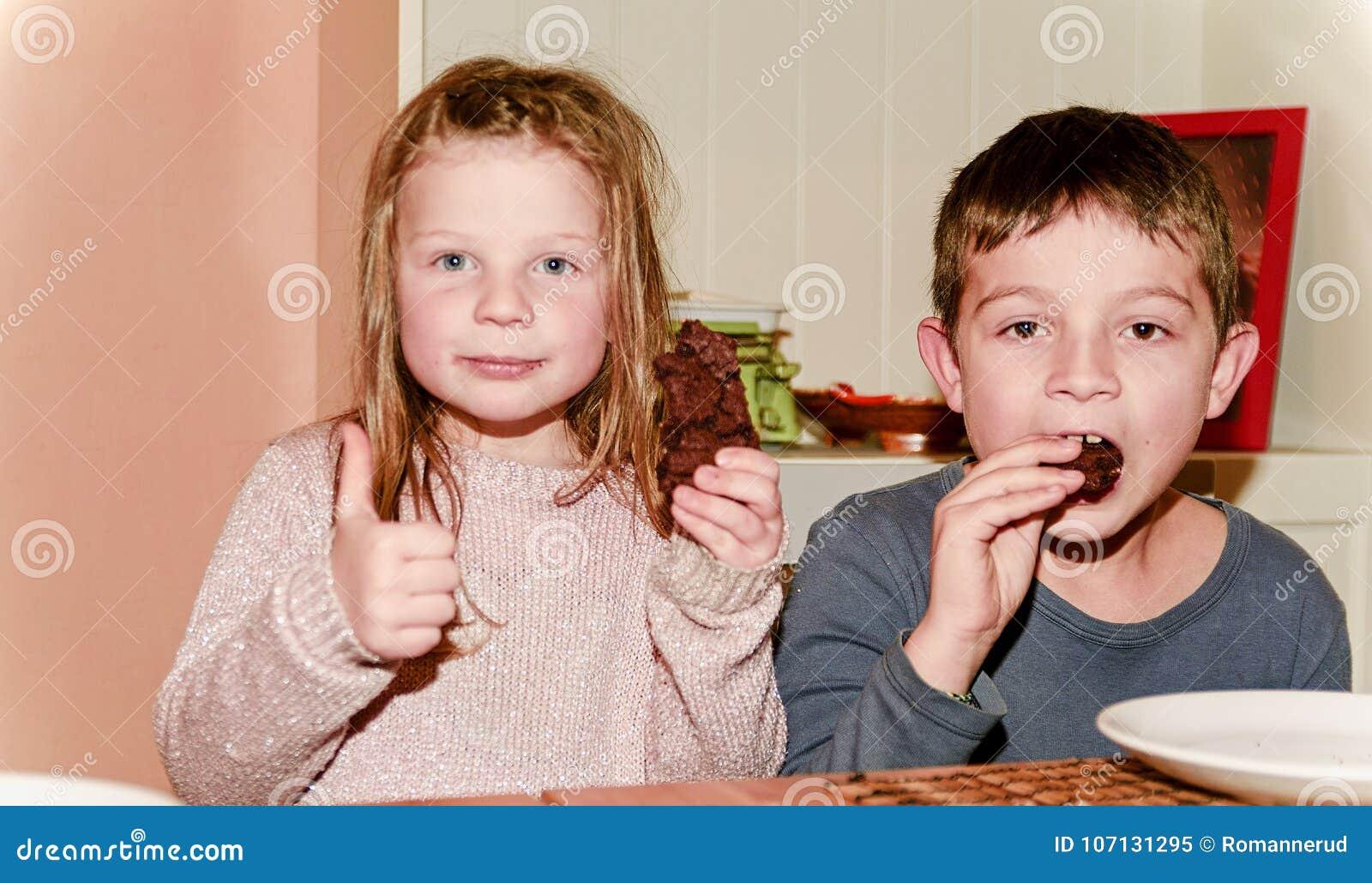 Duas crianças estão comendo cookies que marrons a menina está dando o thum acima Conceito engraçado e das crianças Adicione o efe