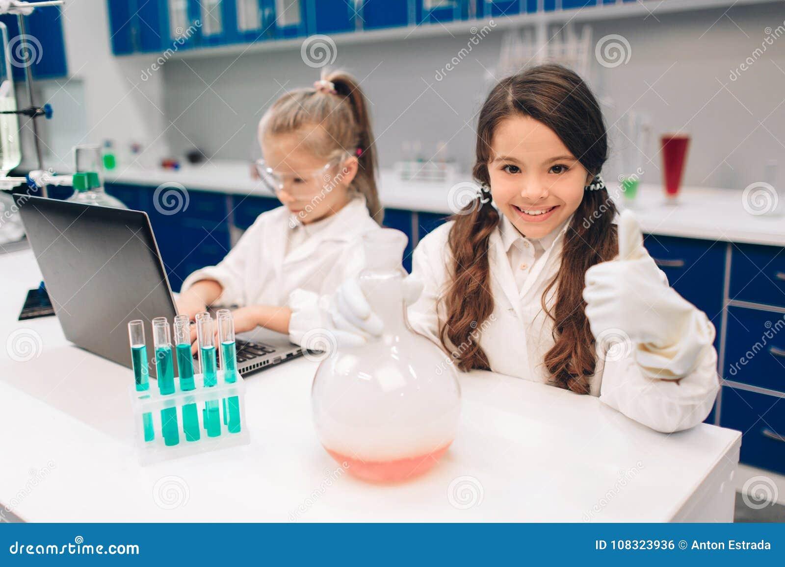 Duas crianças no laboratório revestem a aprendizagem da química no laboratório da escola Cientistas novos na fatura protetora dos