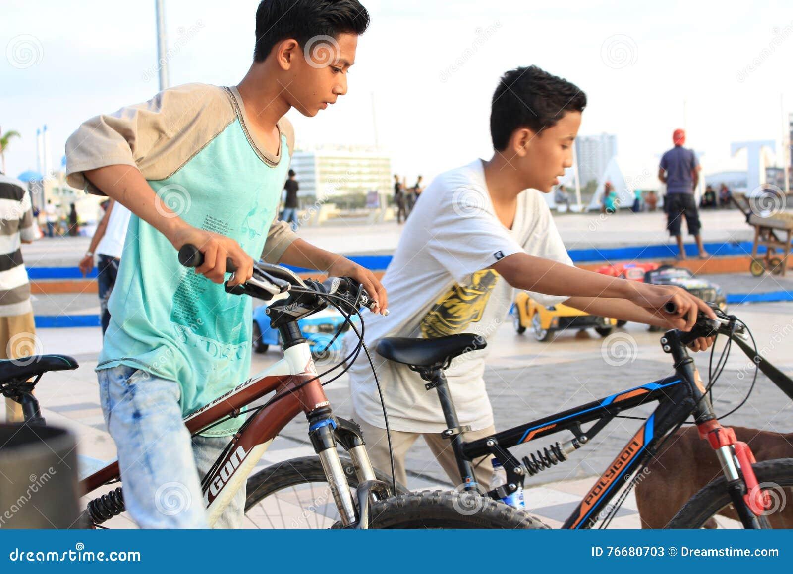 Duas crianças que jogam bicicletas na praia