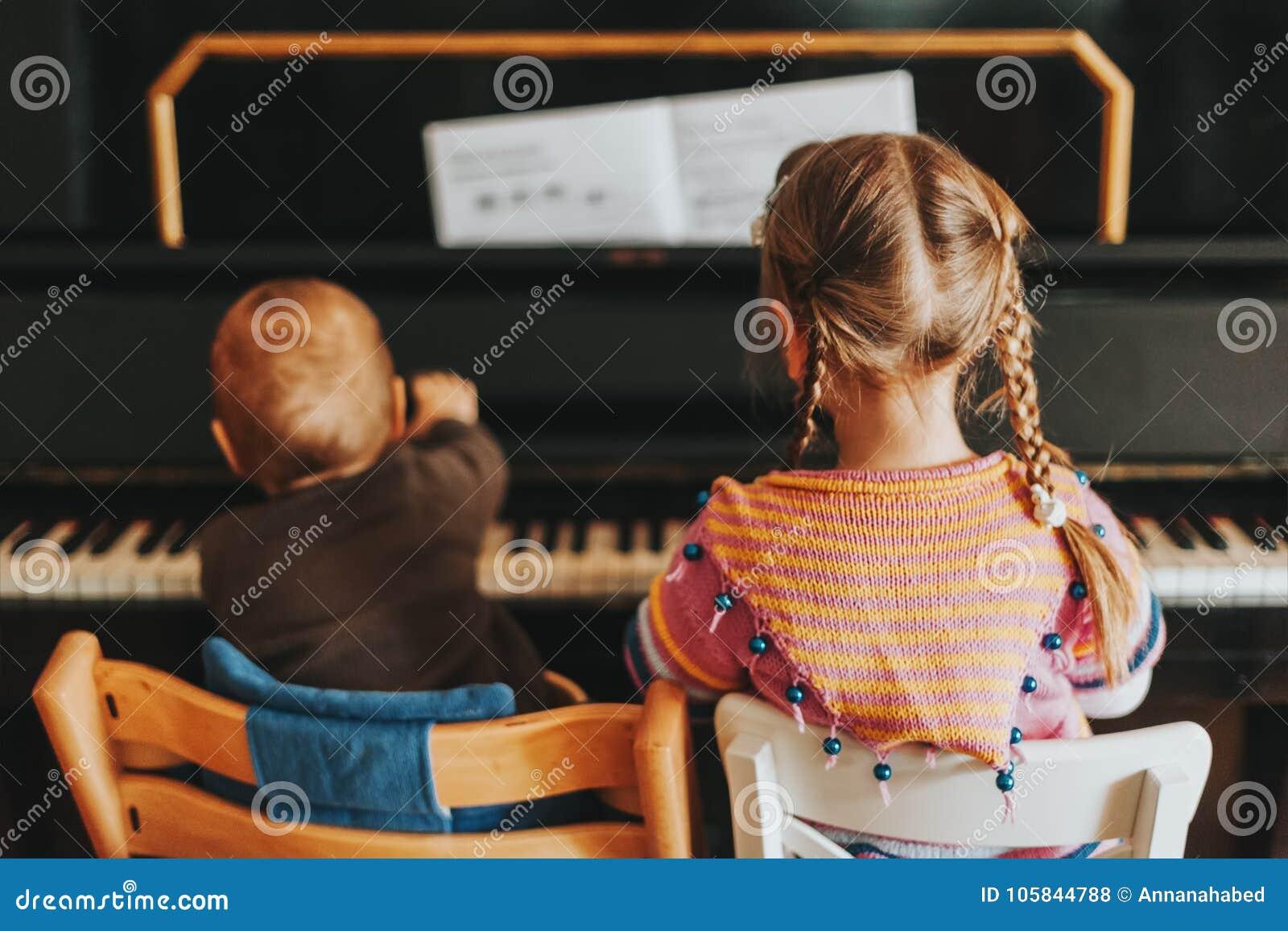 Duas crianças que jogam no piano