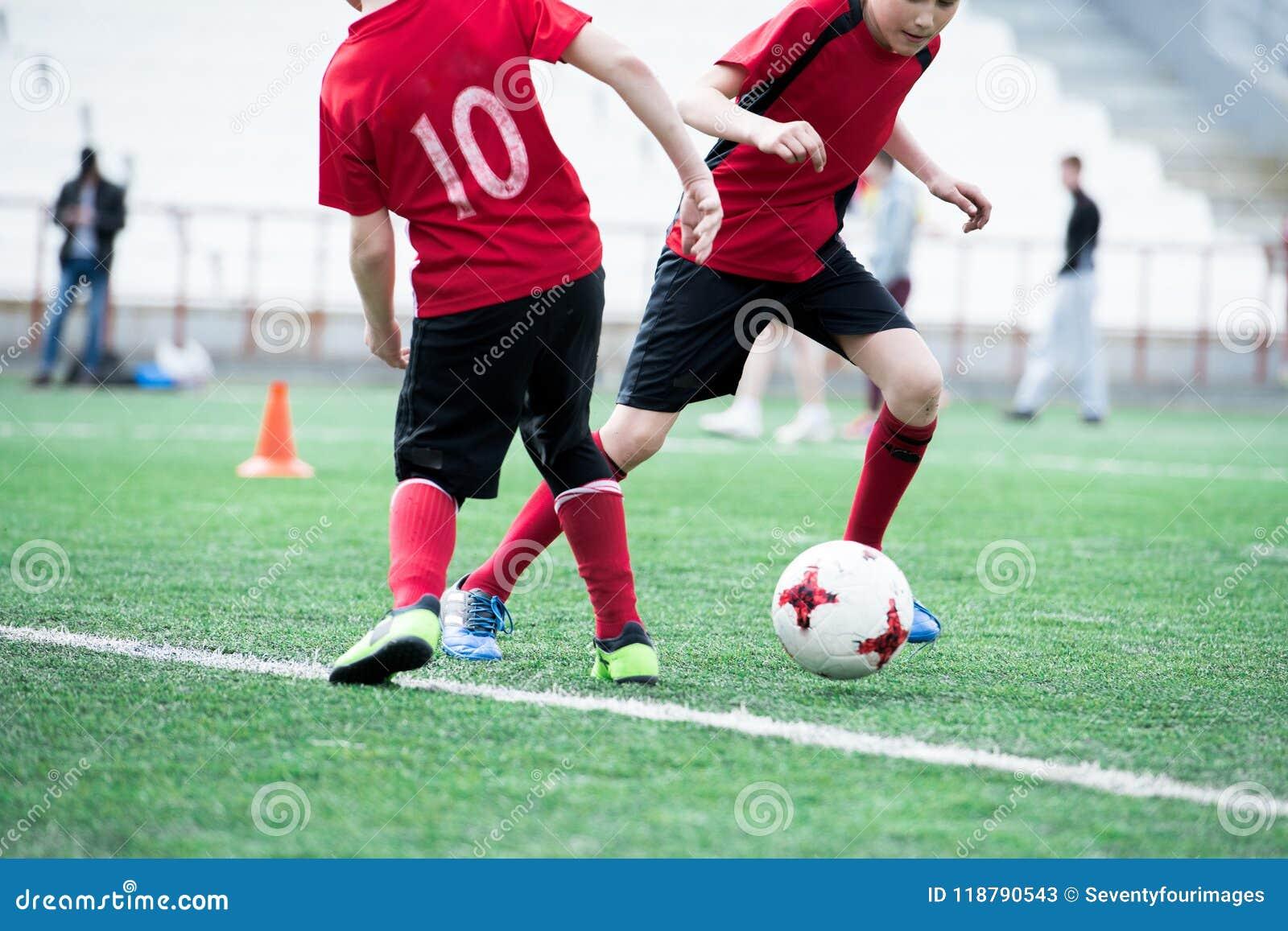 Duas crianças que jogam o futebol