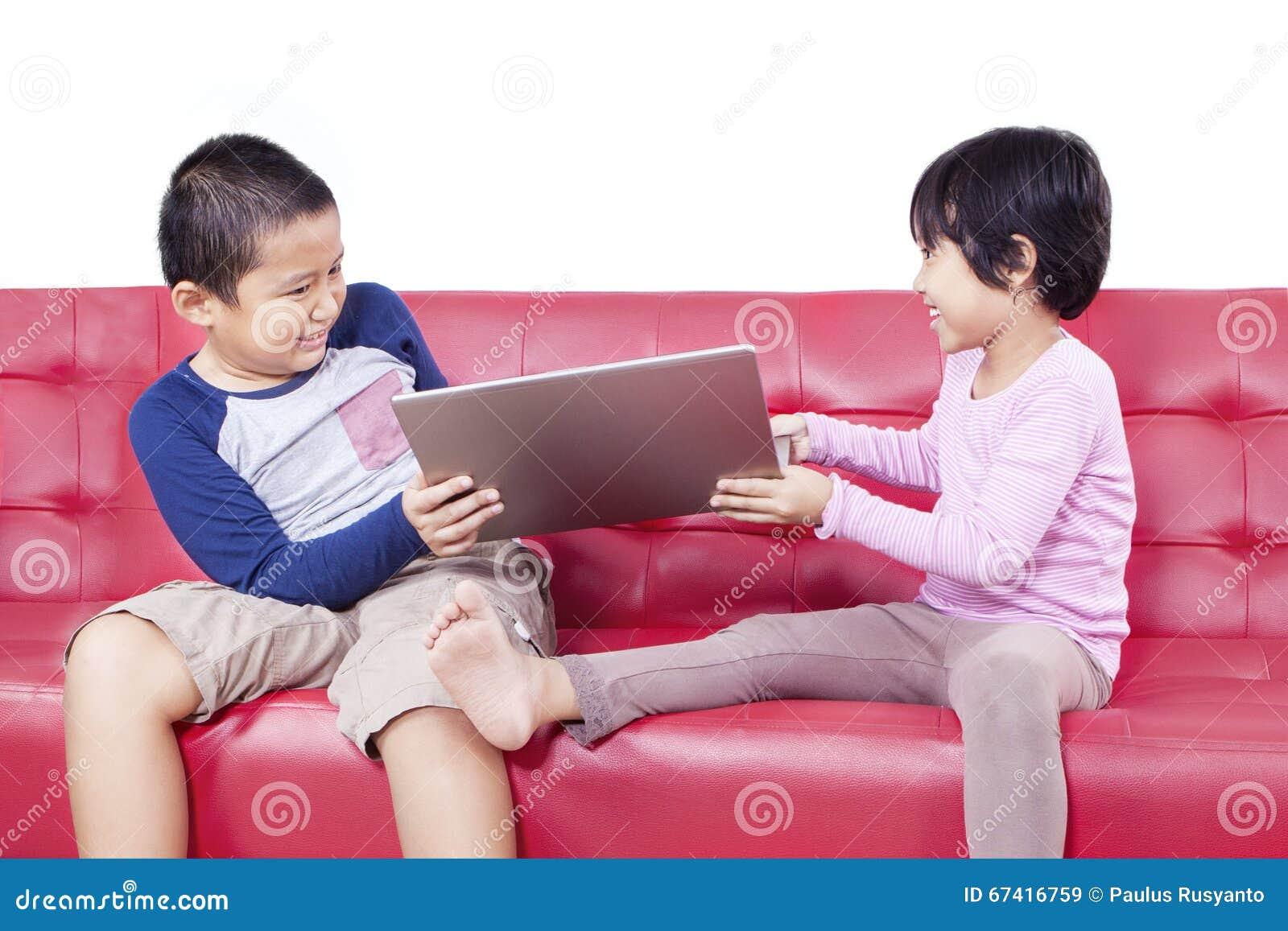 Duas crianças que lutam sobre um portátil