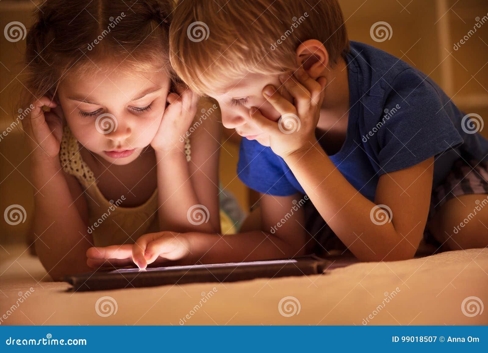 Duas crianças que olham desenhos animados