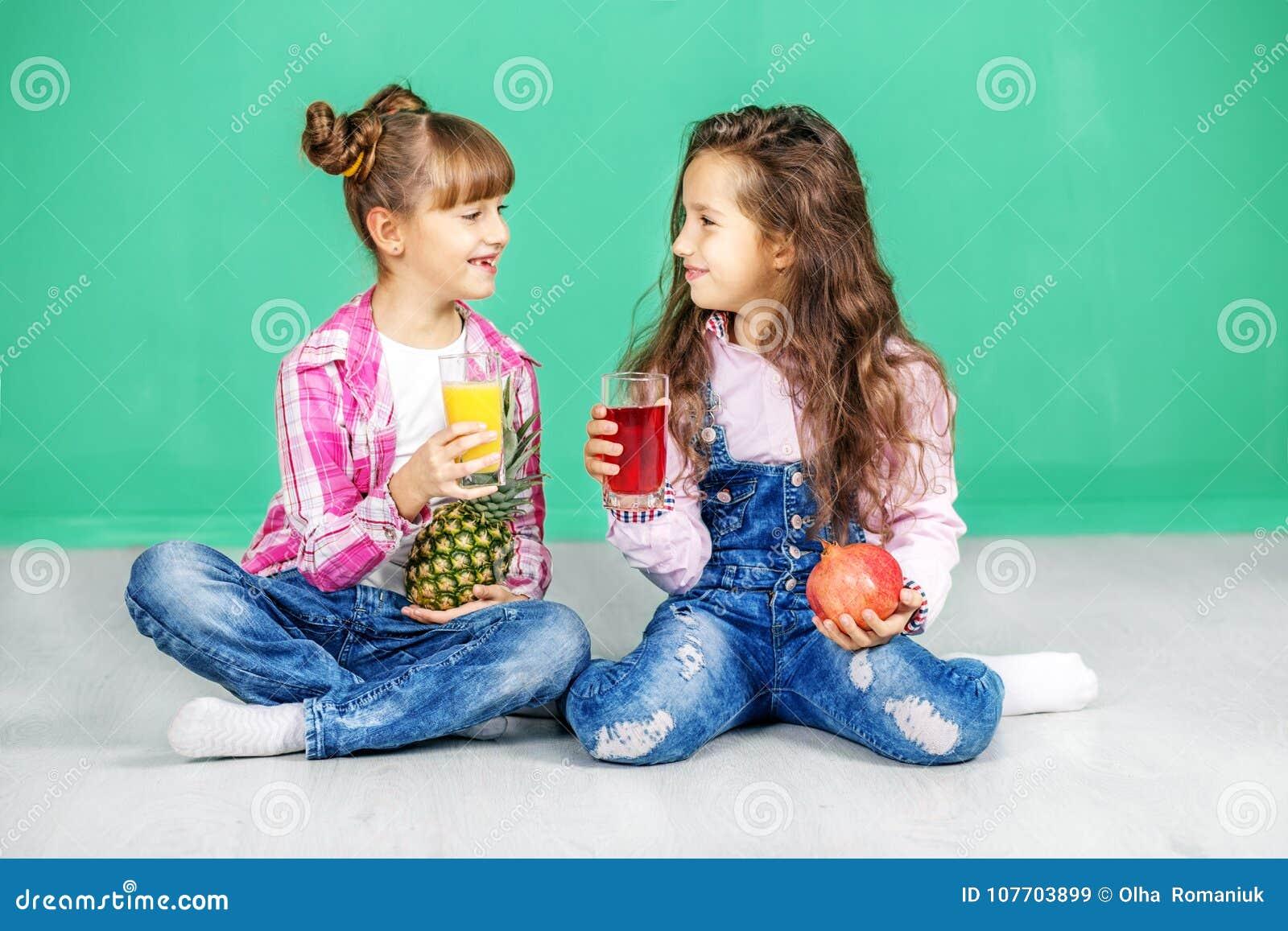 Duas crianças são de fala e bebendo o suco Meninas com pineappl