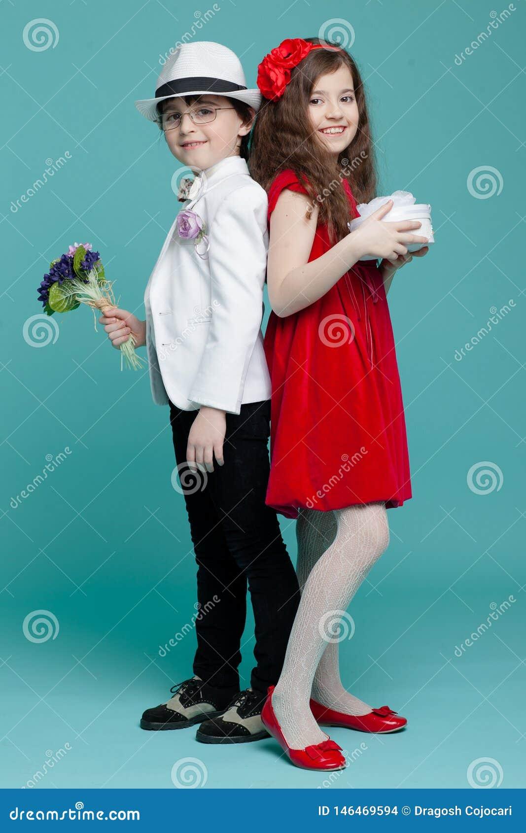 Duas crianças, um menino no terno, vidros do olho, chapéu e menina no vestido vermelho que levanta no estúdio, isolado no fundo d