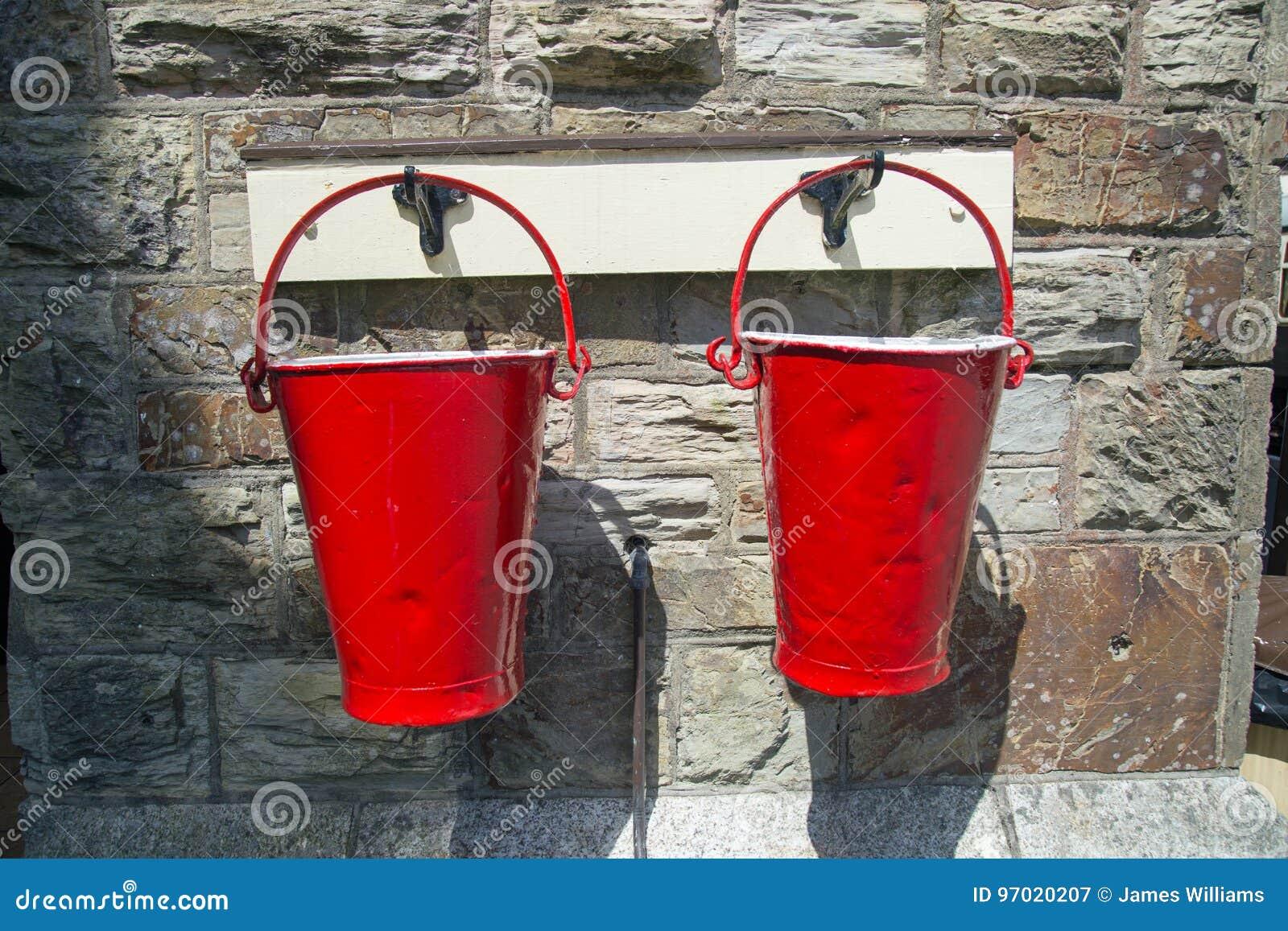 Duas cubetas de fogo vermelho contra um fundo da parede de pedra