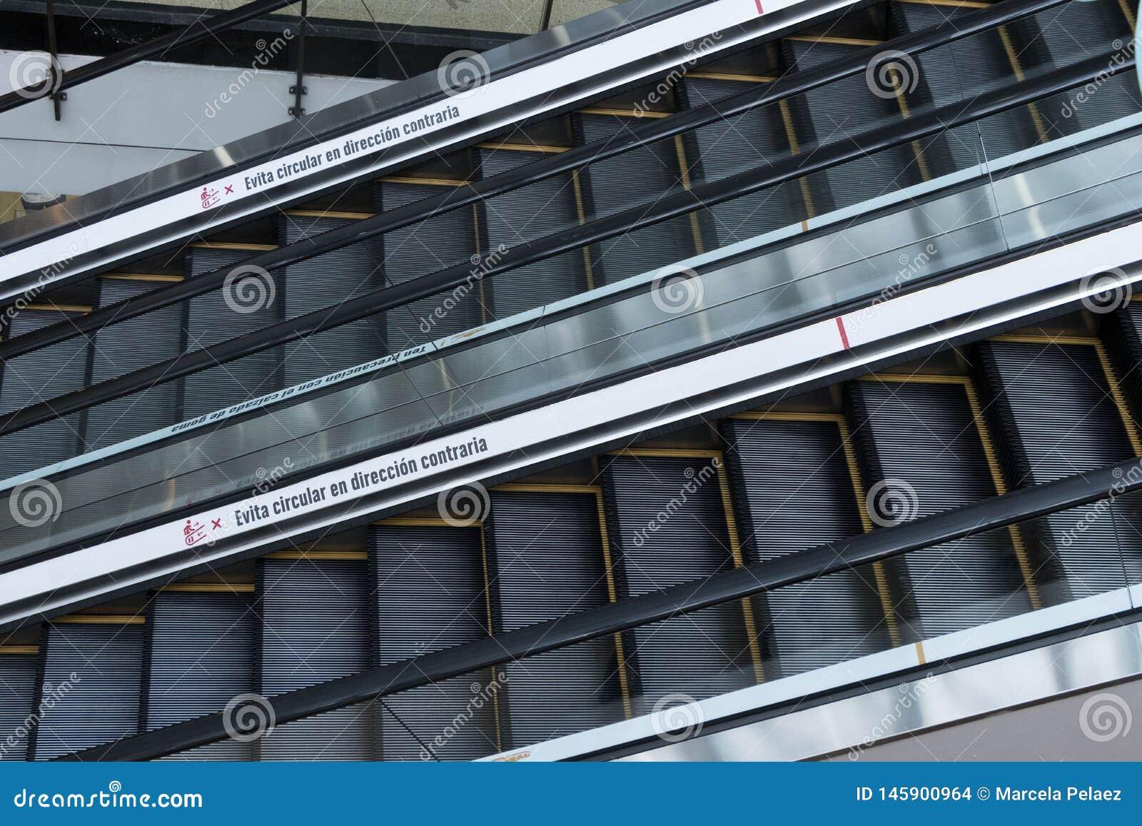 Duas escadas rolantes no primeiro plano com um sinal em espanhol que diz evitam ir no sentido oposto