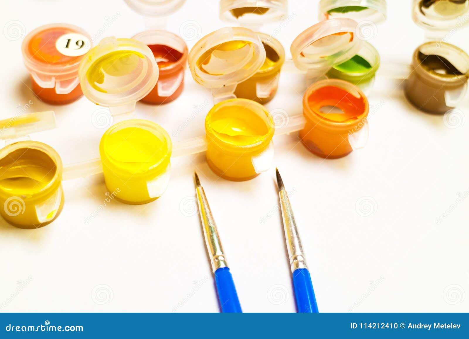 Duas escovas de pintura azuis para a pintura em um fundo branco ao lado deles recipientes com guache da pintura