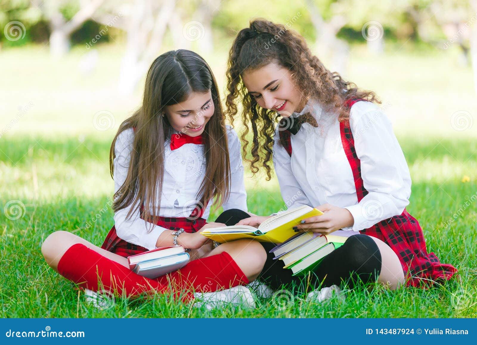 Duas estudantes nas fardas da escola sentam-se com os livros no parque As estudantes ou os estudantes são ensinados lições na nat