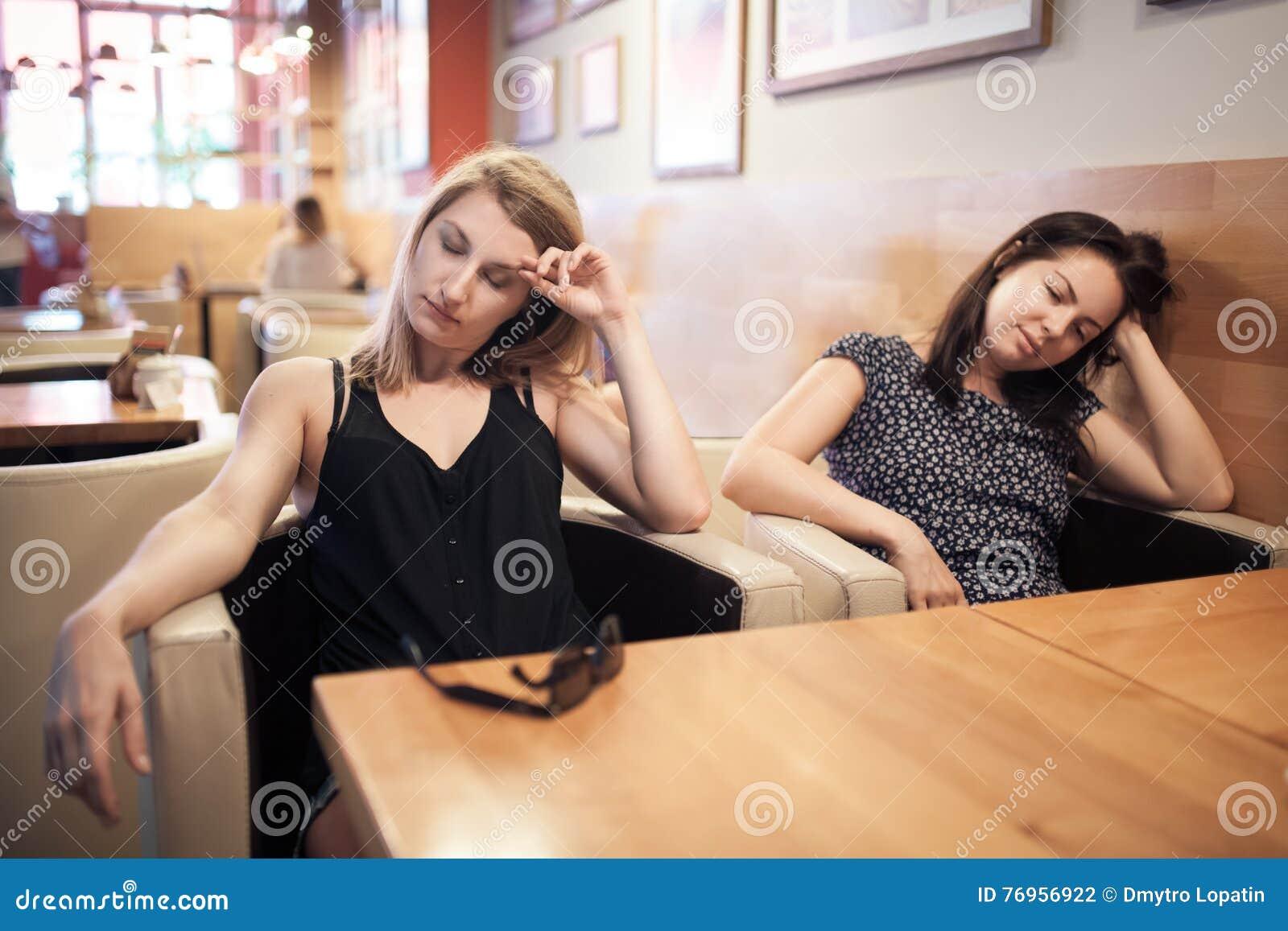 Duas fêmeas cansados que sentam-se no café e no descanso;