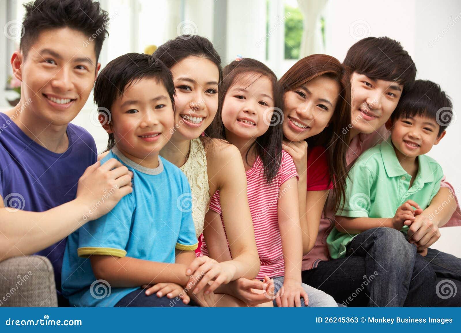 Duas famílias chinesas que sentam-se e que relaxam em casa