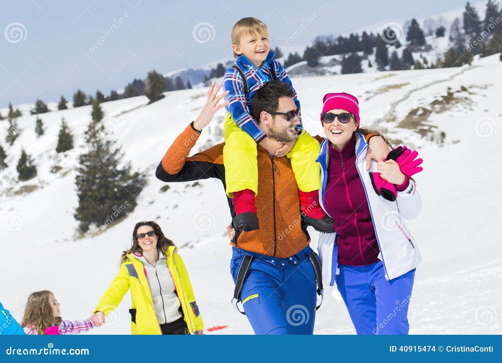 Duas famílias com as crianças que andam na neve