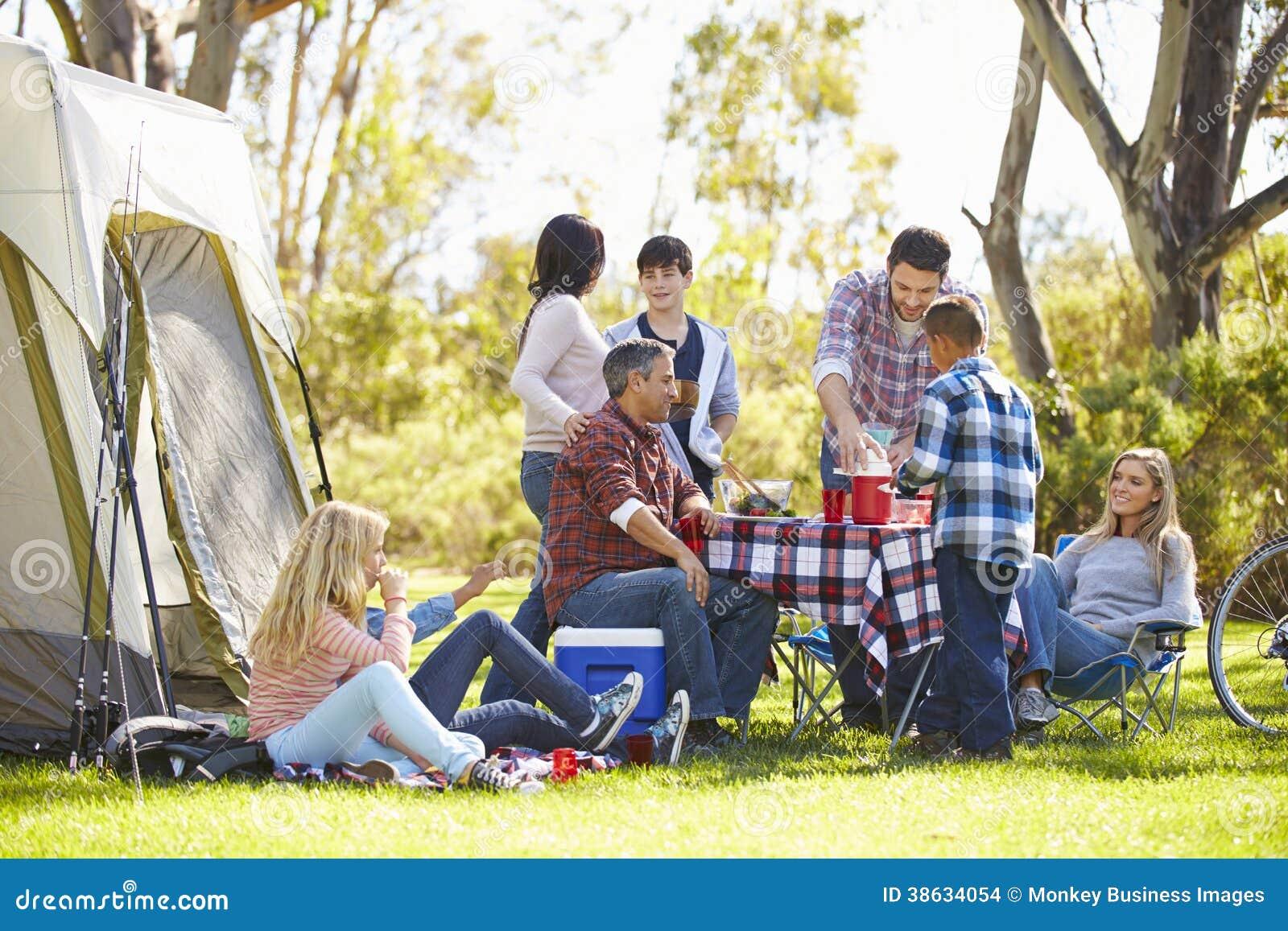 Duas famílias que apreciam o feriado de acampamento no campo